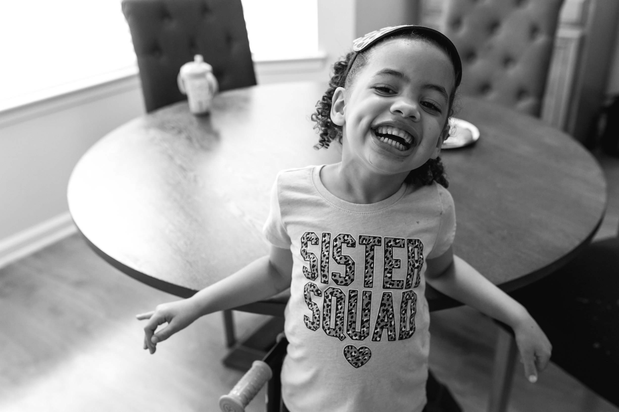 a girl wearing a shirt that says sister squad leans back against a table and smiles