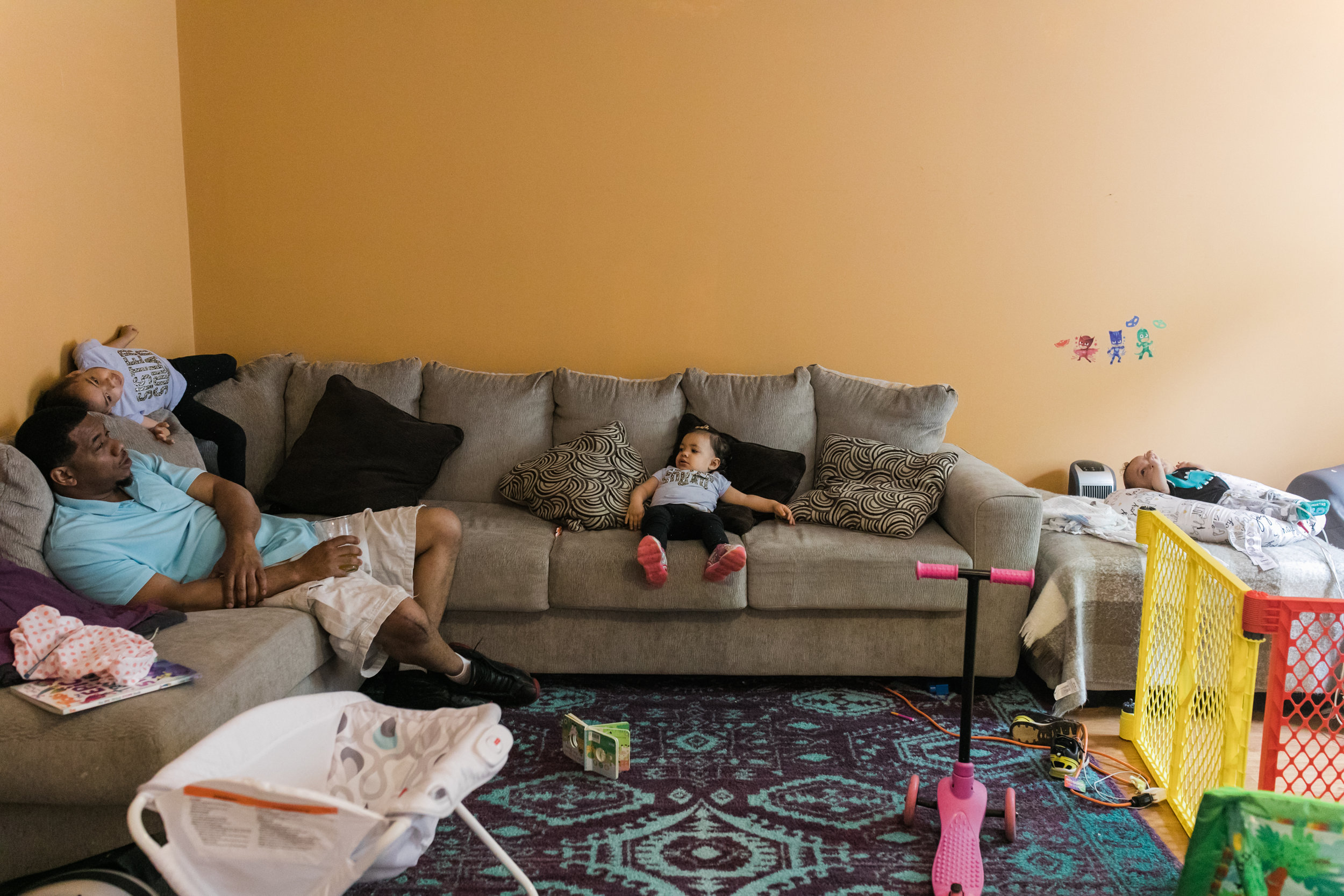 a family lounges on a couch in their living room