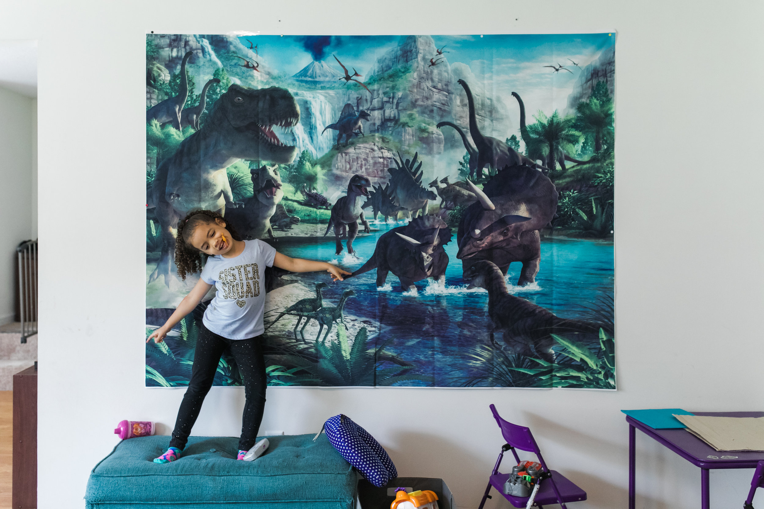 A girl stands on an ottoman in front of a dinosaur poster with a dinosaur toy in her mouth