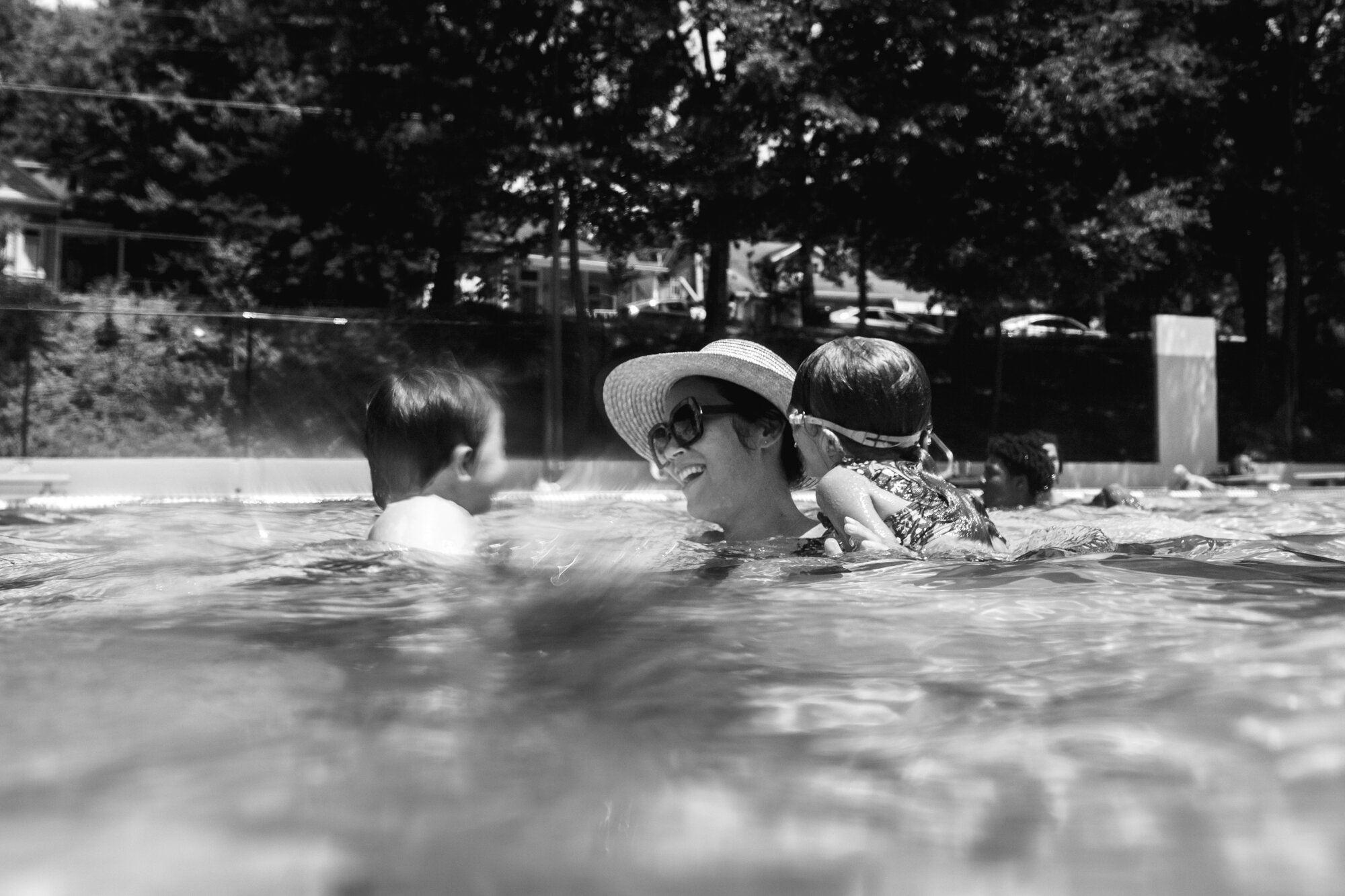 image of a mother smiles at her son in a public pool while her daughter hangs on her shoulder from a day in the life photography session