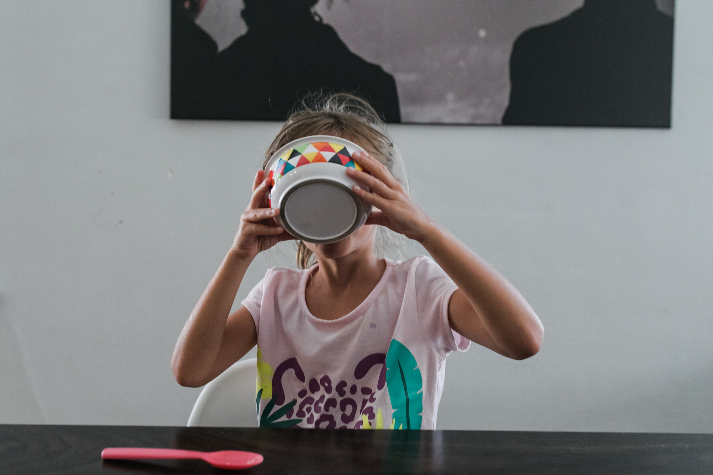 image of a girl drinking milk out of a bowl of cereal from a day in the life photography session