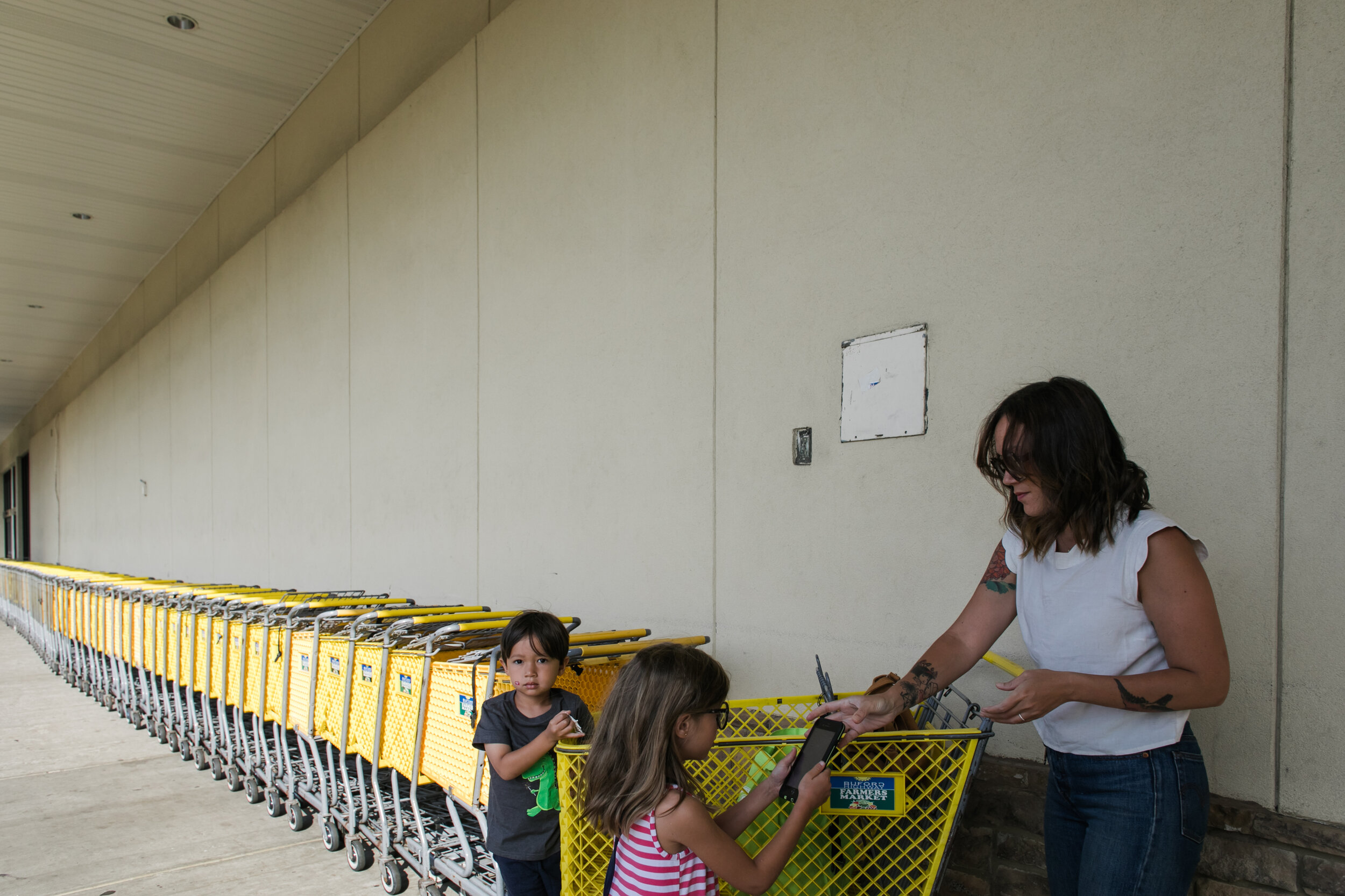image of a boy standing on a cart in front of a long line of carts from a day in the life photography session