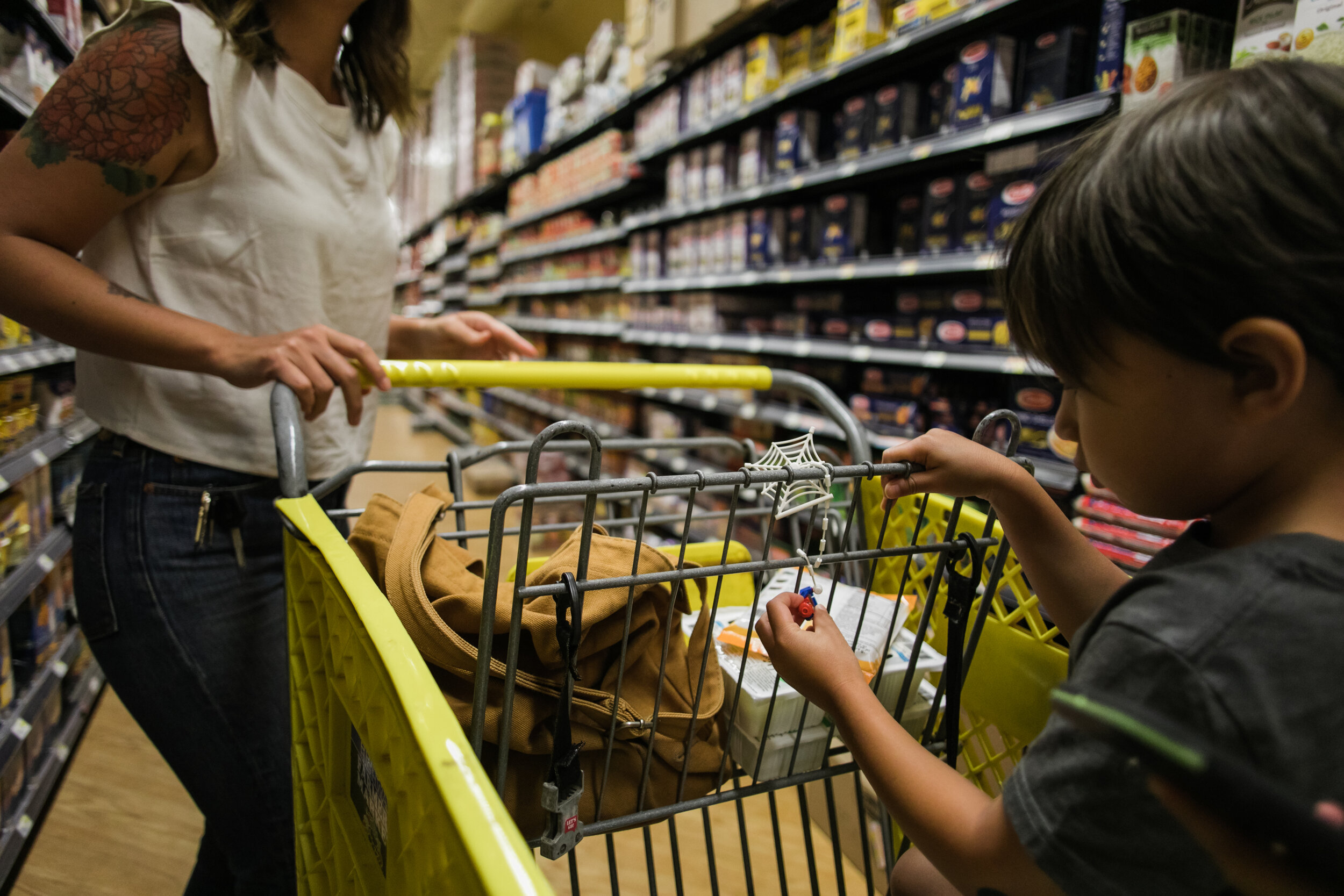 image of a boy sitting in a cart playing with a spiderman toy in a grocery store from a day in the life photography session
