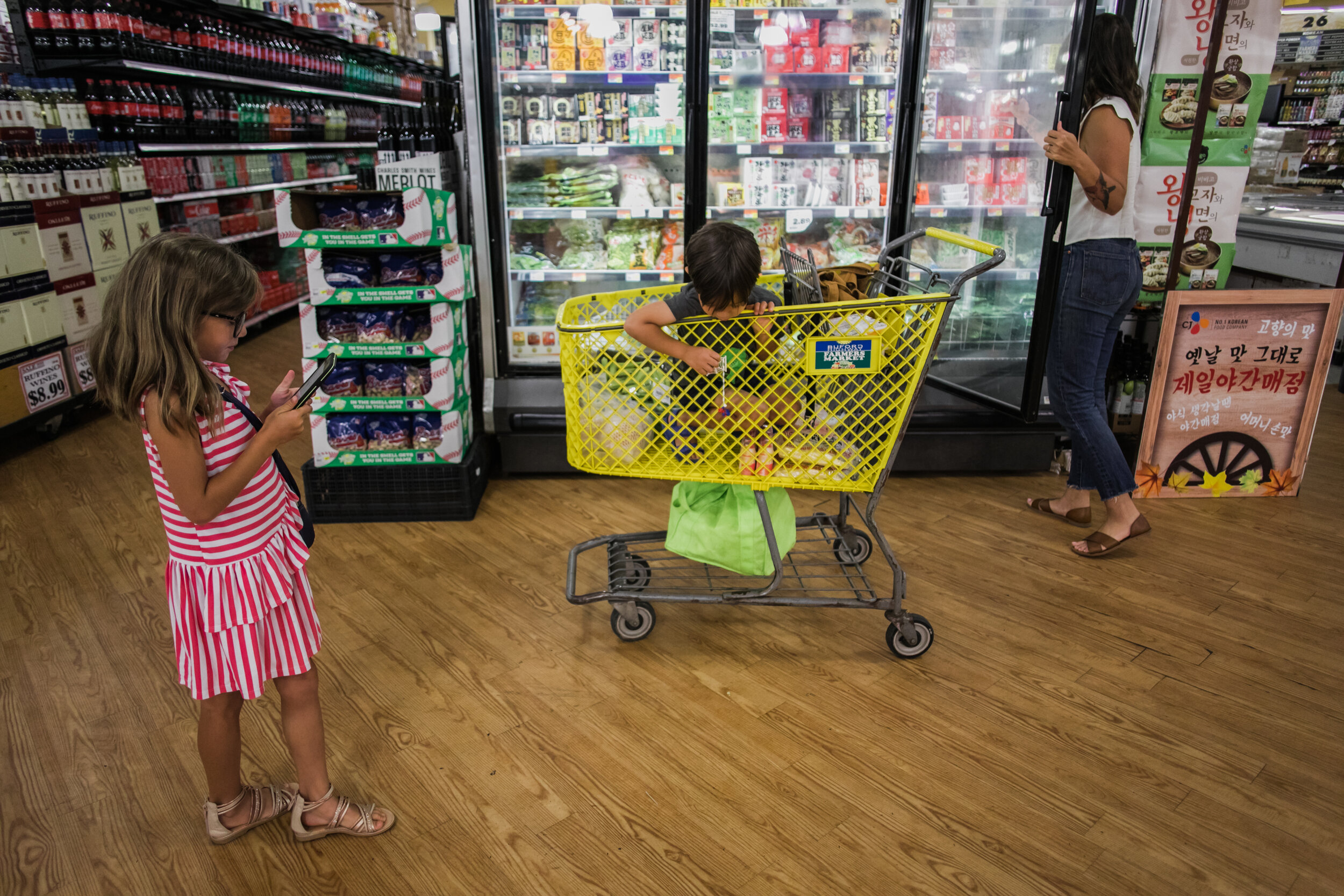 image of a boy sitting in a cart playing with a spiderman toy while his sister reads the grocery list on a phone and his mom grabs food out of a freezer in a grocery store from a day in the life photography session