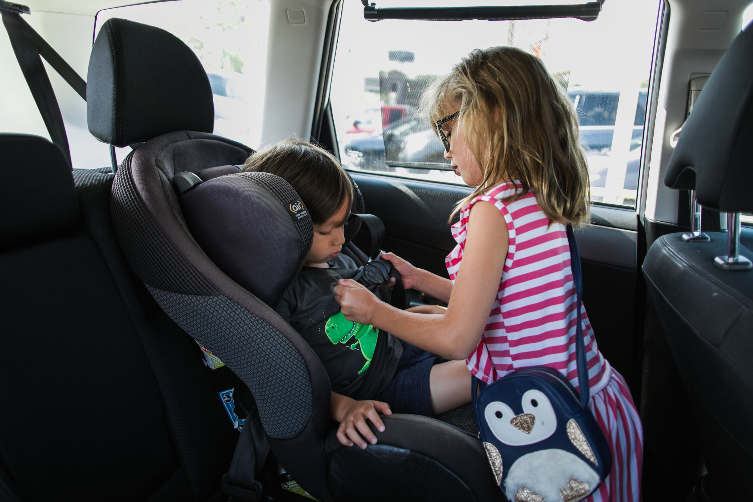 image of a girl helping buckle her little brother into his carseat from a day in the life photography session