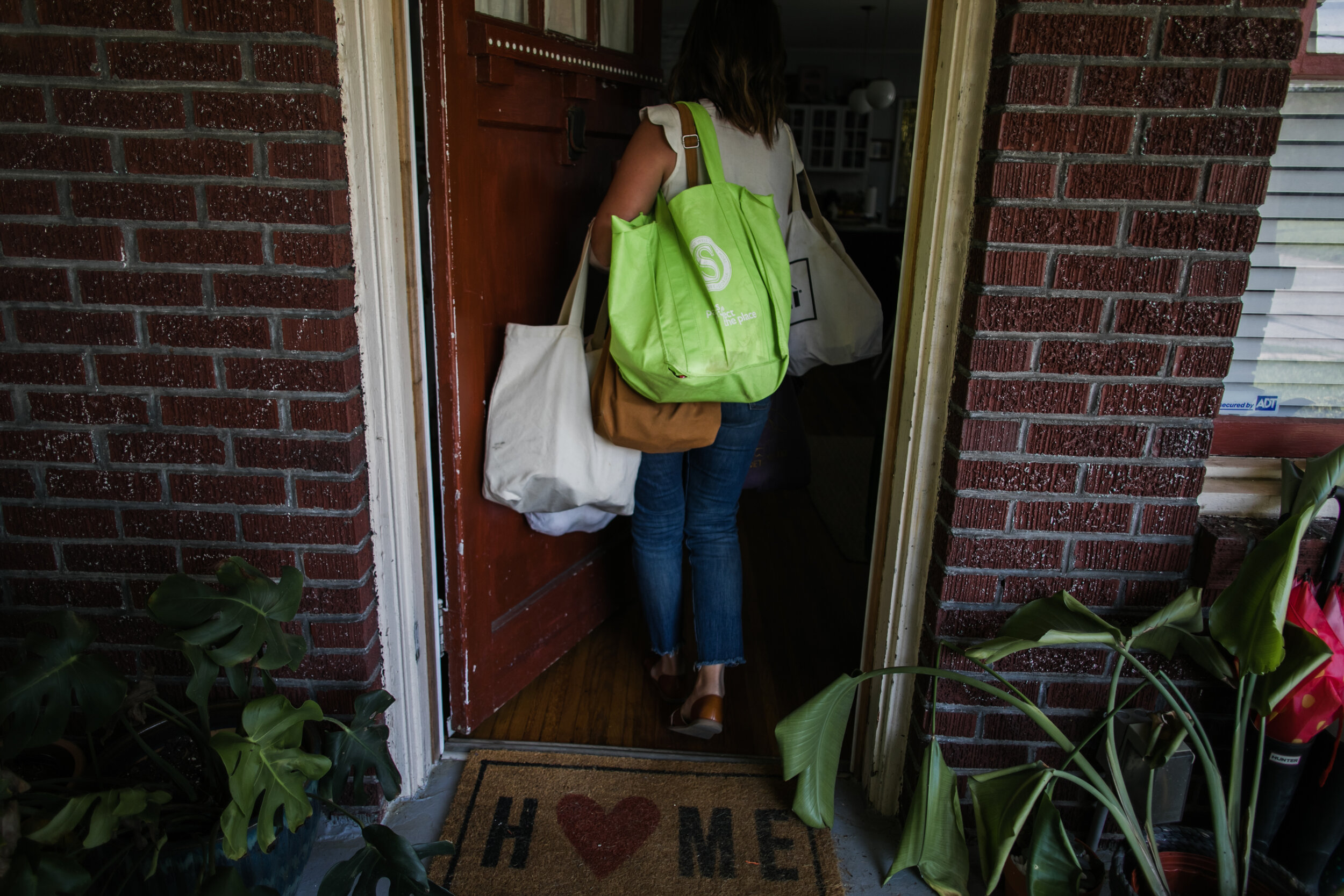 image of a mother carrying all the bags of groceries into her home from a day in the life photography session