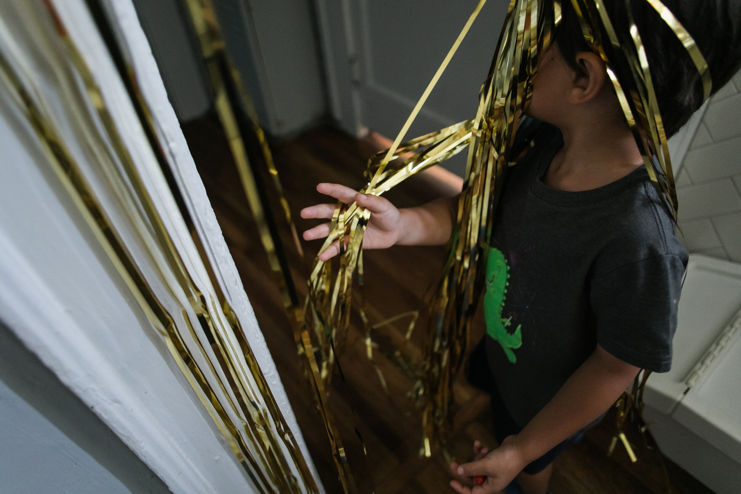 image of a boy playing with tinsel hanging in a doorway from a day in the life photography session