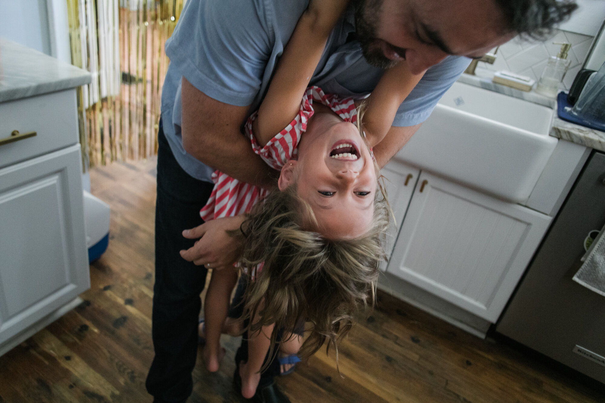 image of a girl hanging from her father's neck smiling from a day in the life photography session