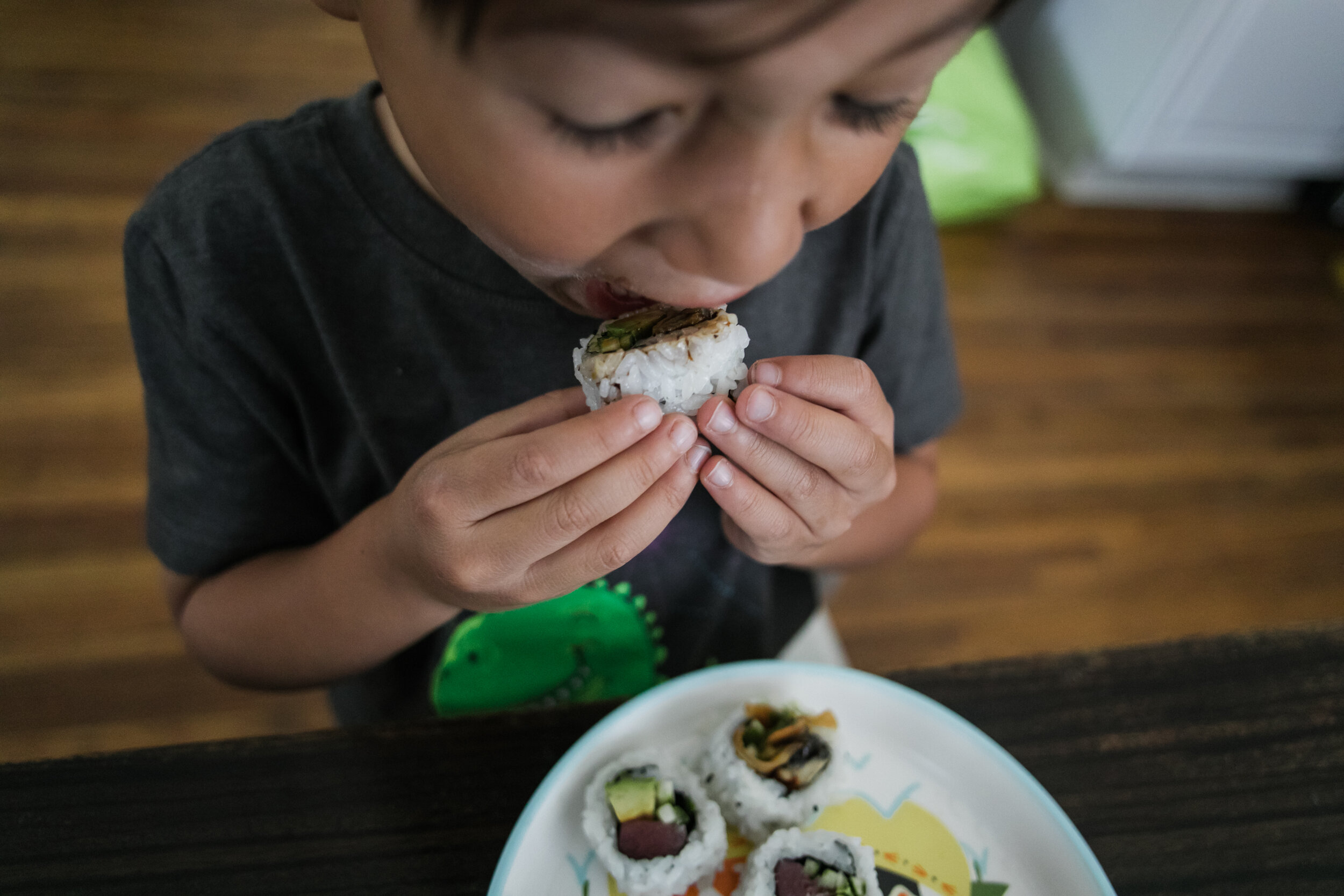 image of a boy biting into a sushi roll from a day in the life photography session