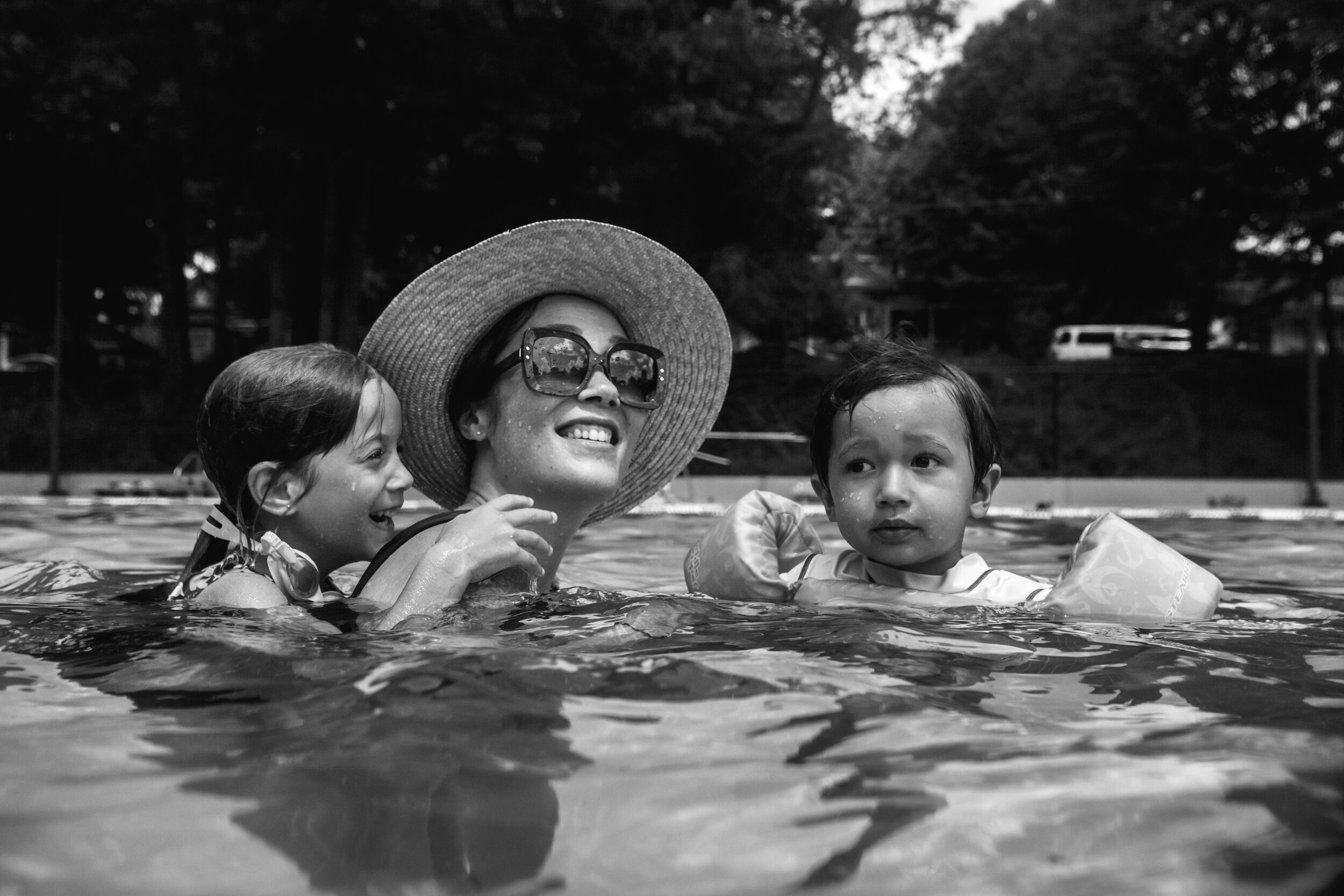 image of a mother with her two children in the pool from a day in the life photography session