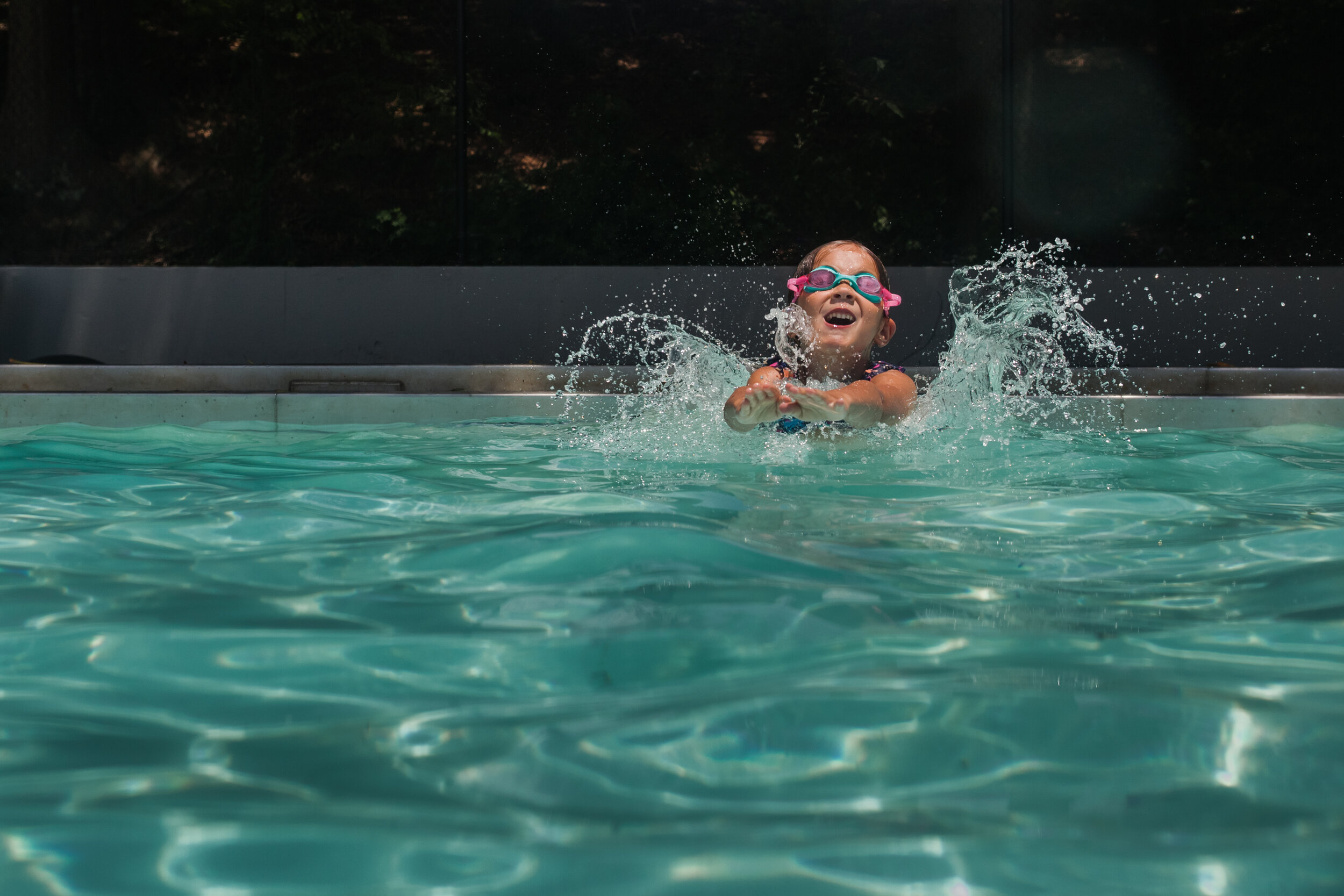 image of a girl swimming in a pool from a day in the life photography session