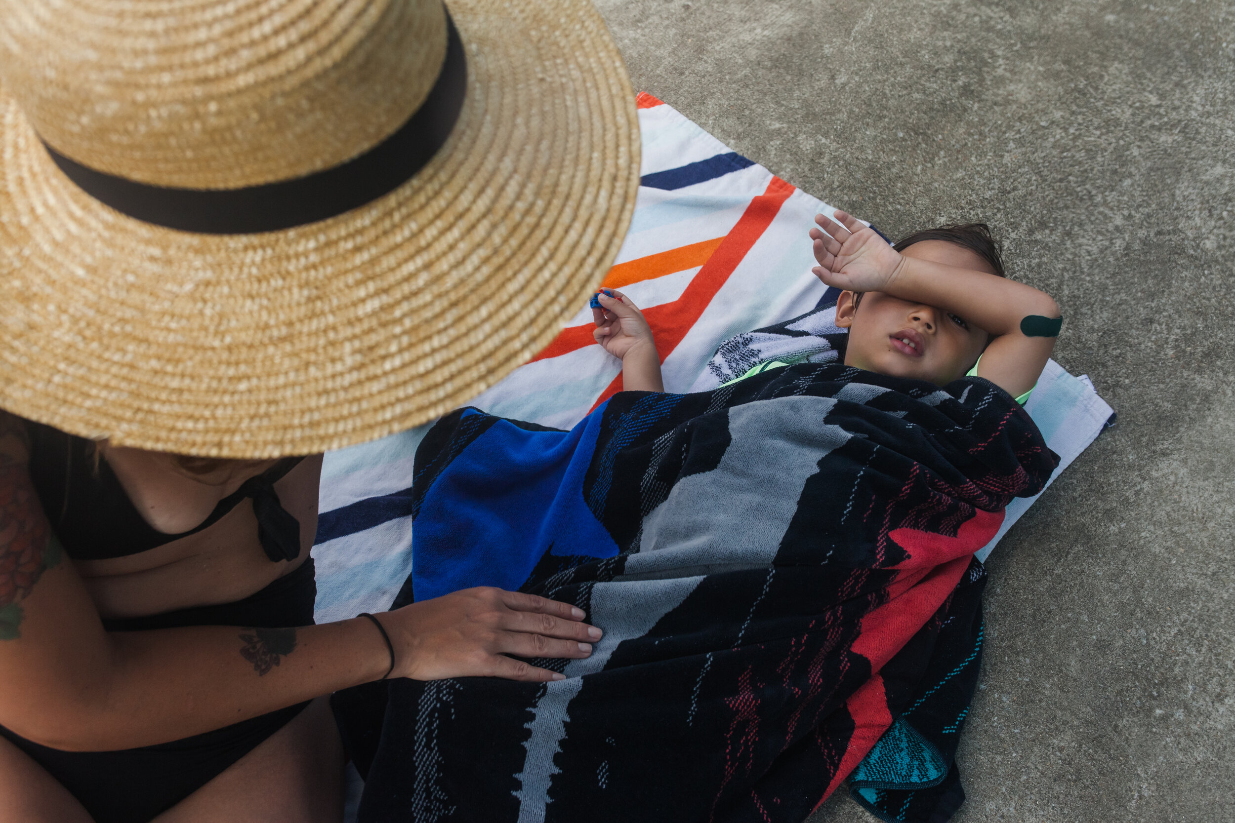 image of a mother looking over her son who is drying off on a towel at the pool from a day in the life photography session