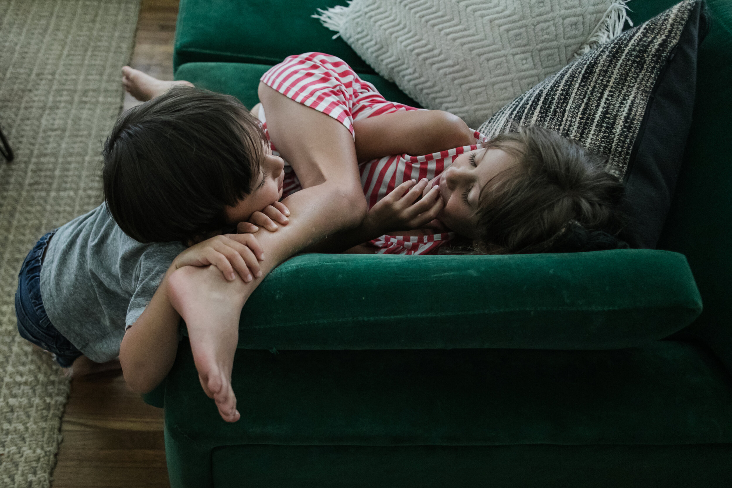 image of a boy holding onto his sister's leg while looking at her from a day in the life photography session