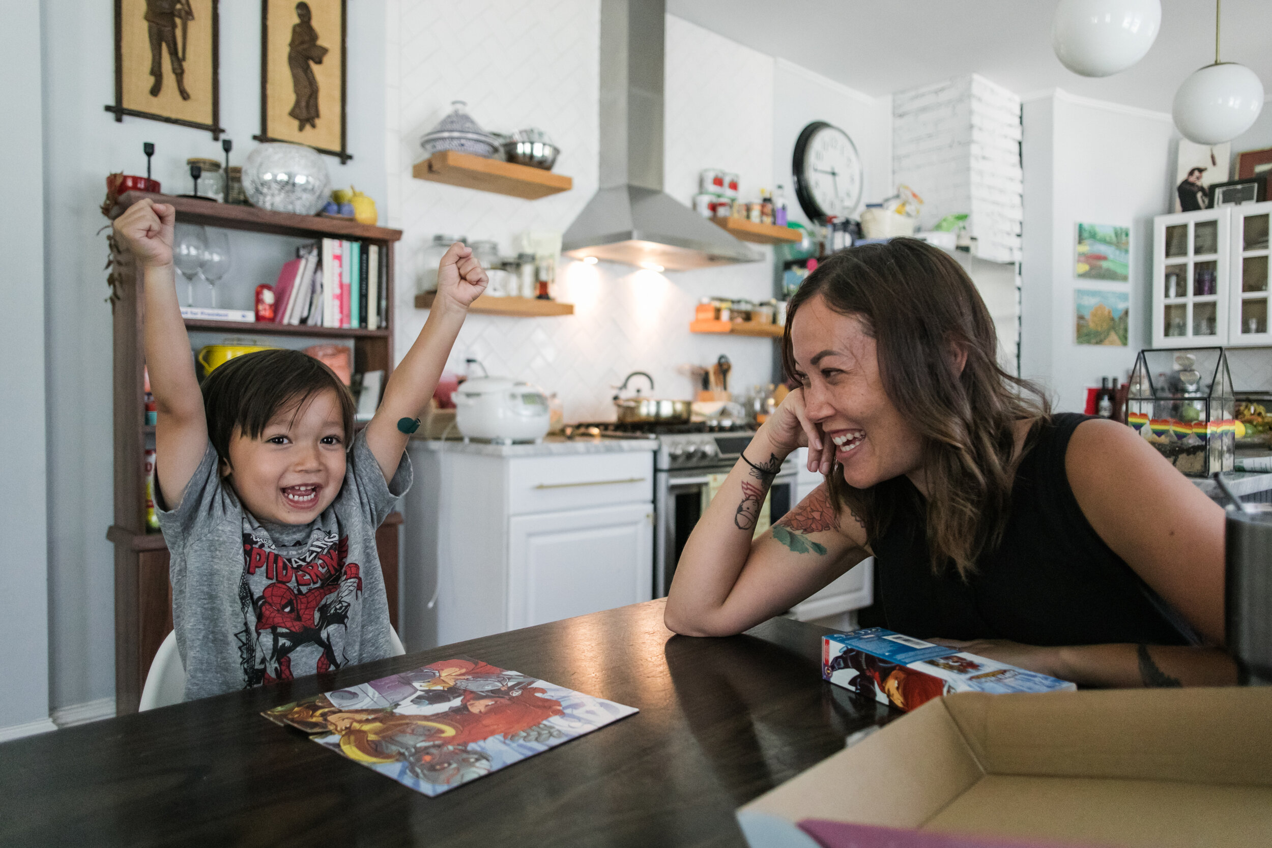 image of a mom smiling at her son who has his arms up in triumph after finishing a puzzle from a day in the life photography session