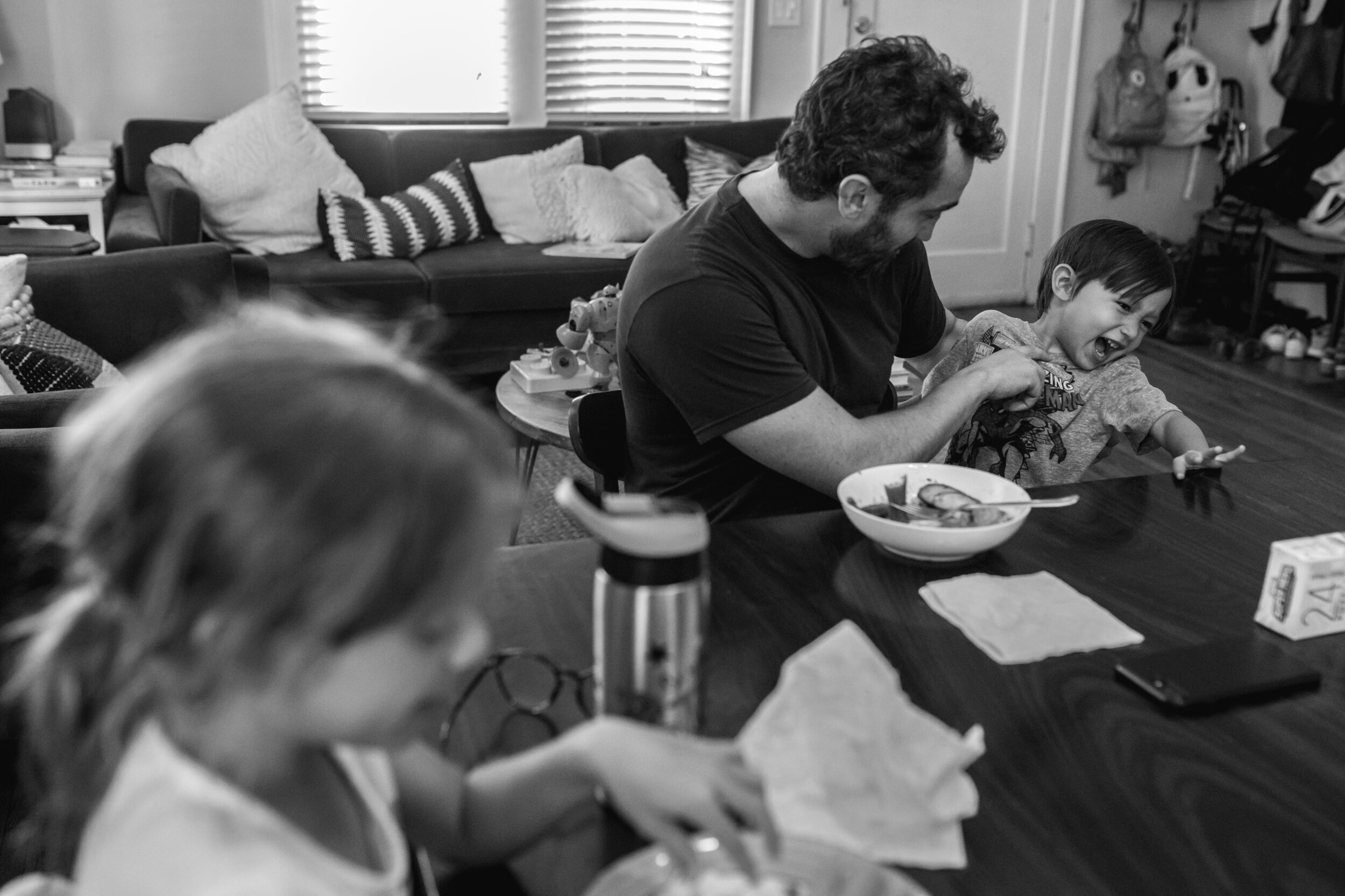 image of a dad playing with his son during dinner from a day in the life photography session