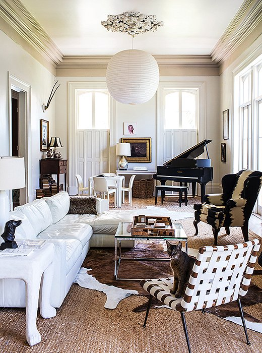 "Sara tried numerous rugs atop the jute flooring before settling on the pony skins, which offer an interesting shape. The family cat, Sparkly Darkly Doo, sits atop a vintage Robsjohn-Gibbings chair bought ""back when you could find these things for a song."""