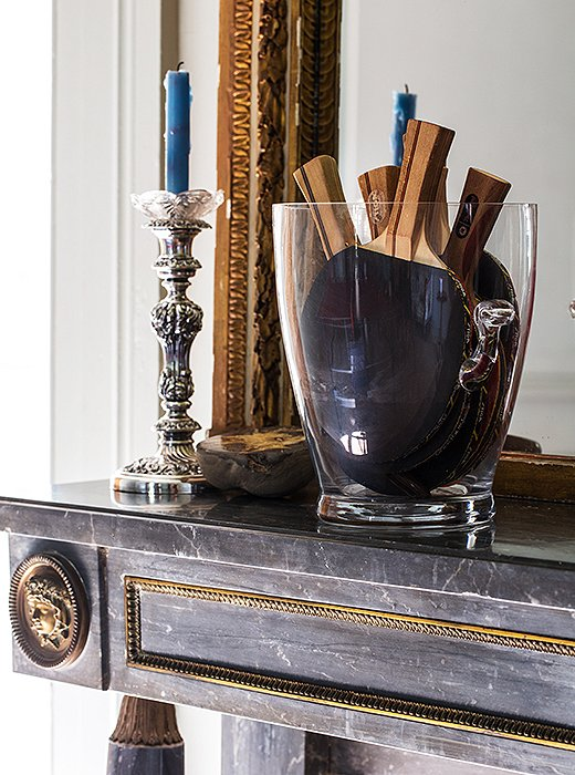 Illustrating her casual way with traditional pieces, Sara stores the ping-pong paddles in an ice bucket alongside an antique silver candlestick.