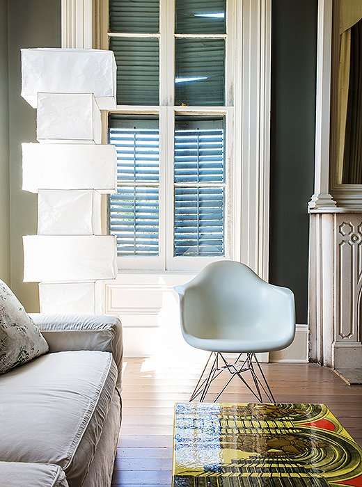 In the bedroom seating area, the gleaming white Eames chair and Noguchi lamp echo the bed's pale geometry and modern feel. A Fornasetti table adds a bit of color.