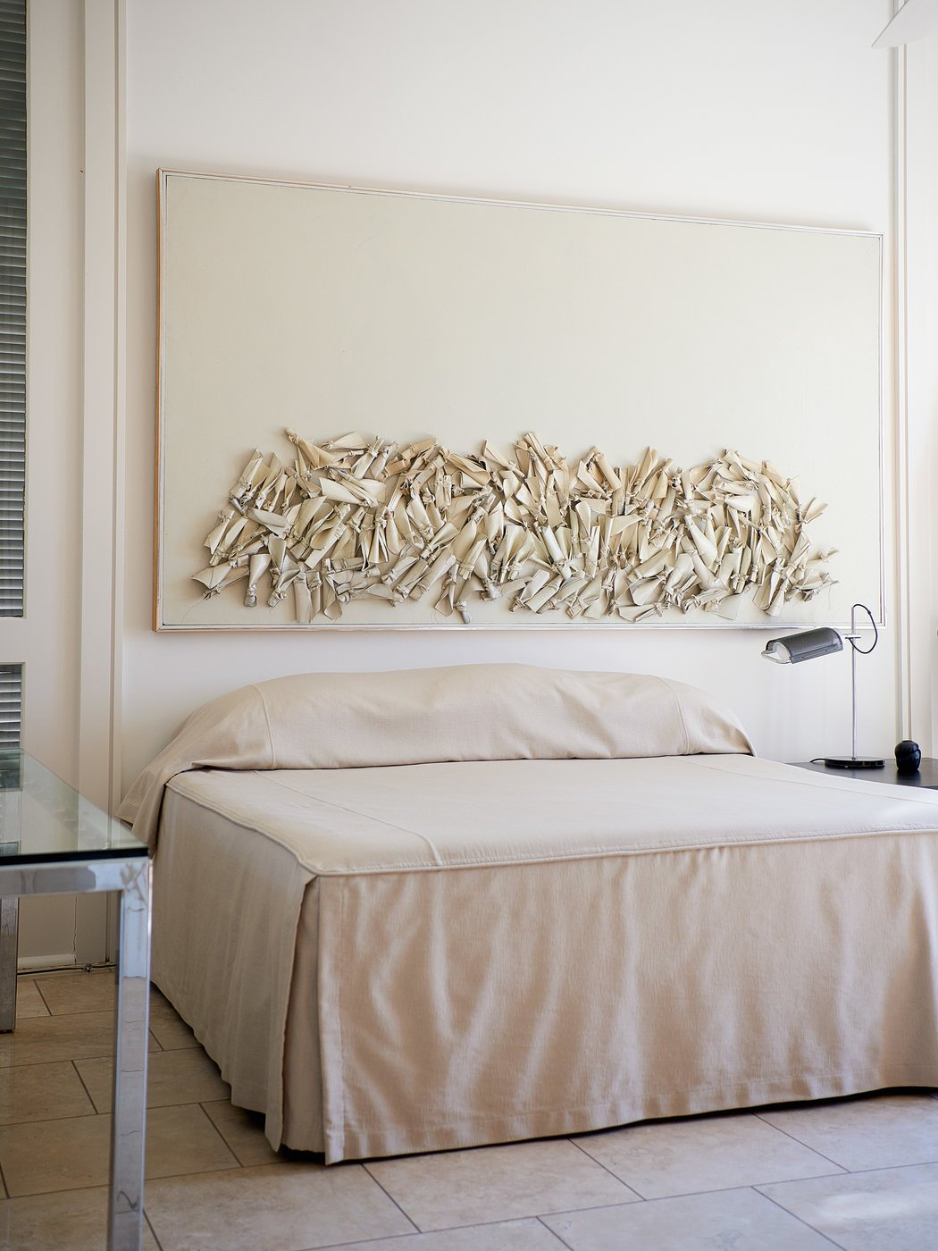 A nine-foot-long painting from Dunbar's 1984 Rag Series collection hangs above his bed. Credit Paul Costello