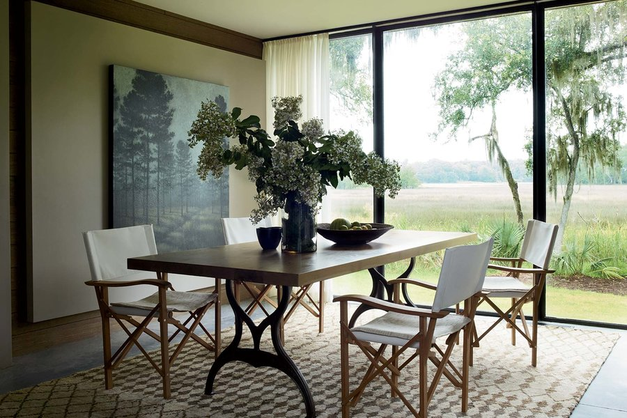 In the dining room, Liaigre chairs surround a custom table from Skylar Morgan on a hemp rug from Ralph Lauren Home.  Simon Upton