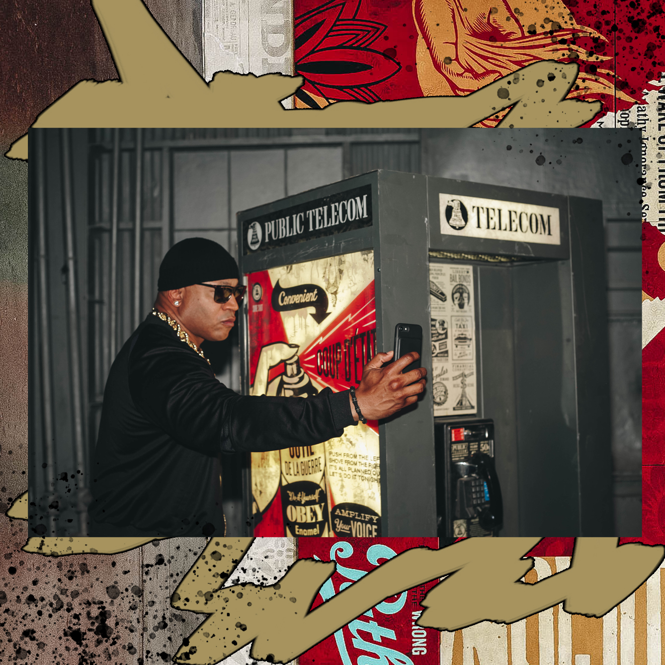 """LL COOL J VISITS SHEPARD FAIREY'S """"DAMAGED"""" EXHIBIT AND POSES IN FRONT OF JOHN TRACY'S PHONE BOOTH INSTALLATION / PHOTO CREDIT: SHEPARD FAIREY / DESIGN CREDIT: VANESSA ACOSTA"""