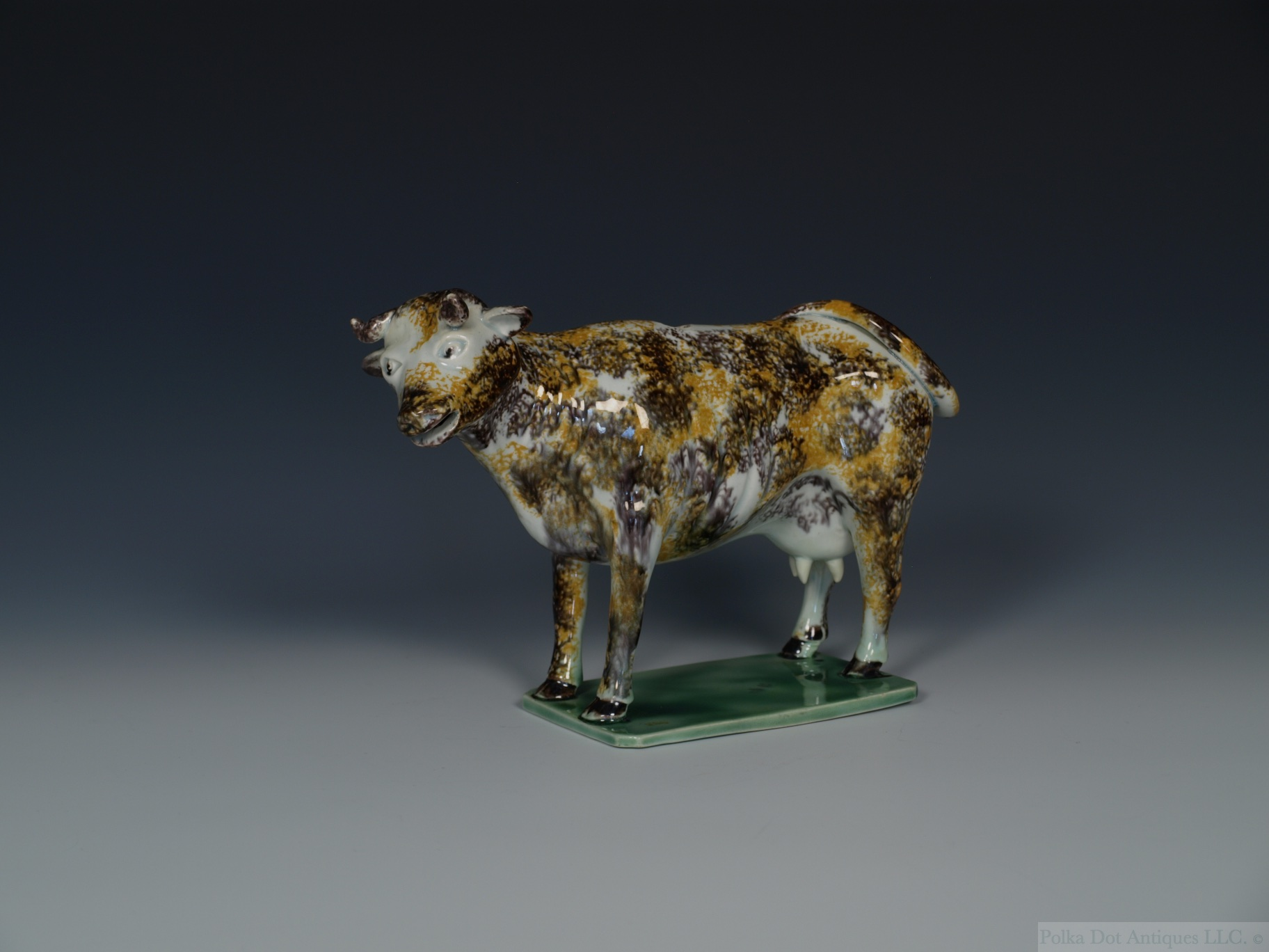 A Staffordshire Pearlware Cow Creamer, c.1800, sponged in ochre and manganese, lacking cover.