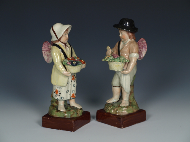 "Pair of Staffordshire Pearlware figures of Cupids Disguised as Vendors, c.1810, 7""."