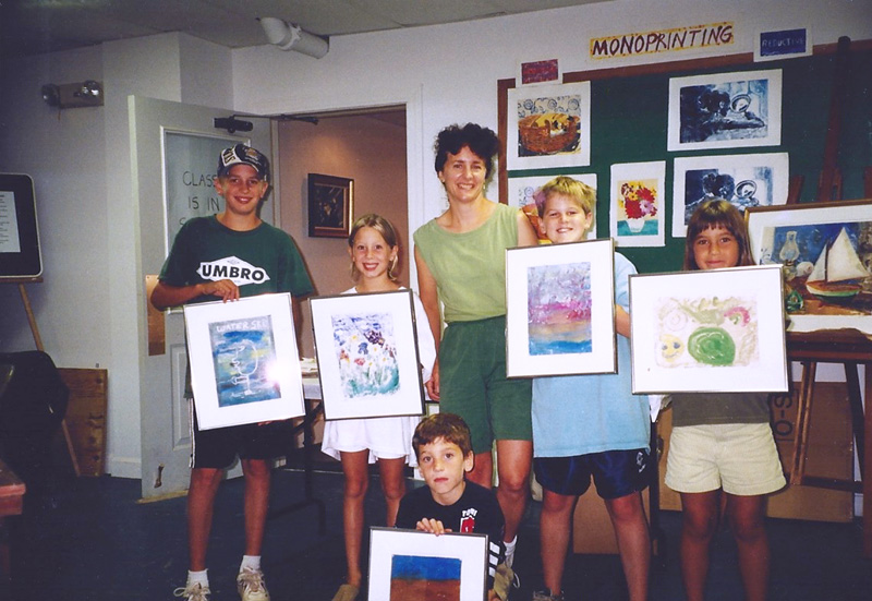 Teresa Baksa with  Explorers of The Art World  students, Cape Cod Museum of Art, Dennis, MA, 2000. This monotype workshop concluded with each child learning the proper way to frame and protect a work of art.