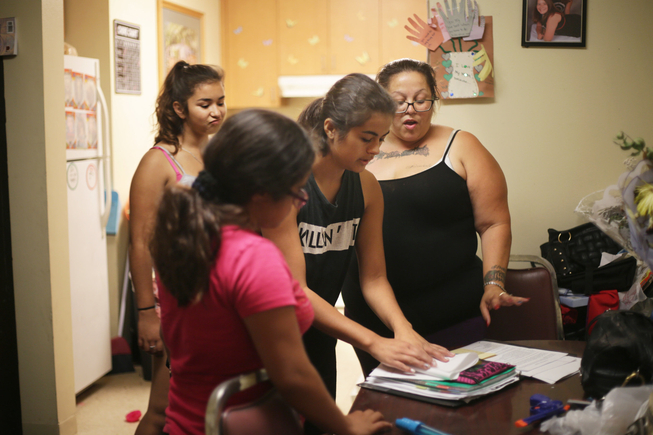 Karina 10, Rios's niece, her daughters Mona, 18, and Viviana, 14, help Rios with her school project. Rios decided to go back to school to become a drug an alcohol counselor after being addicted to drugs for many years.
