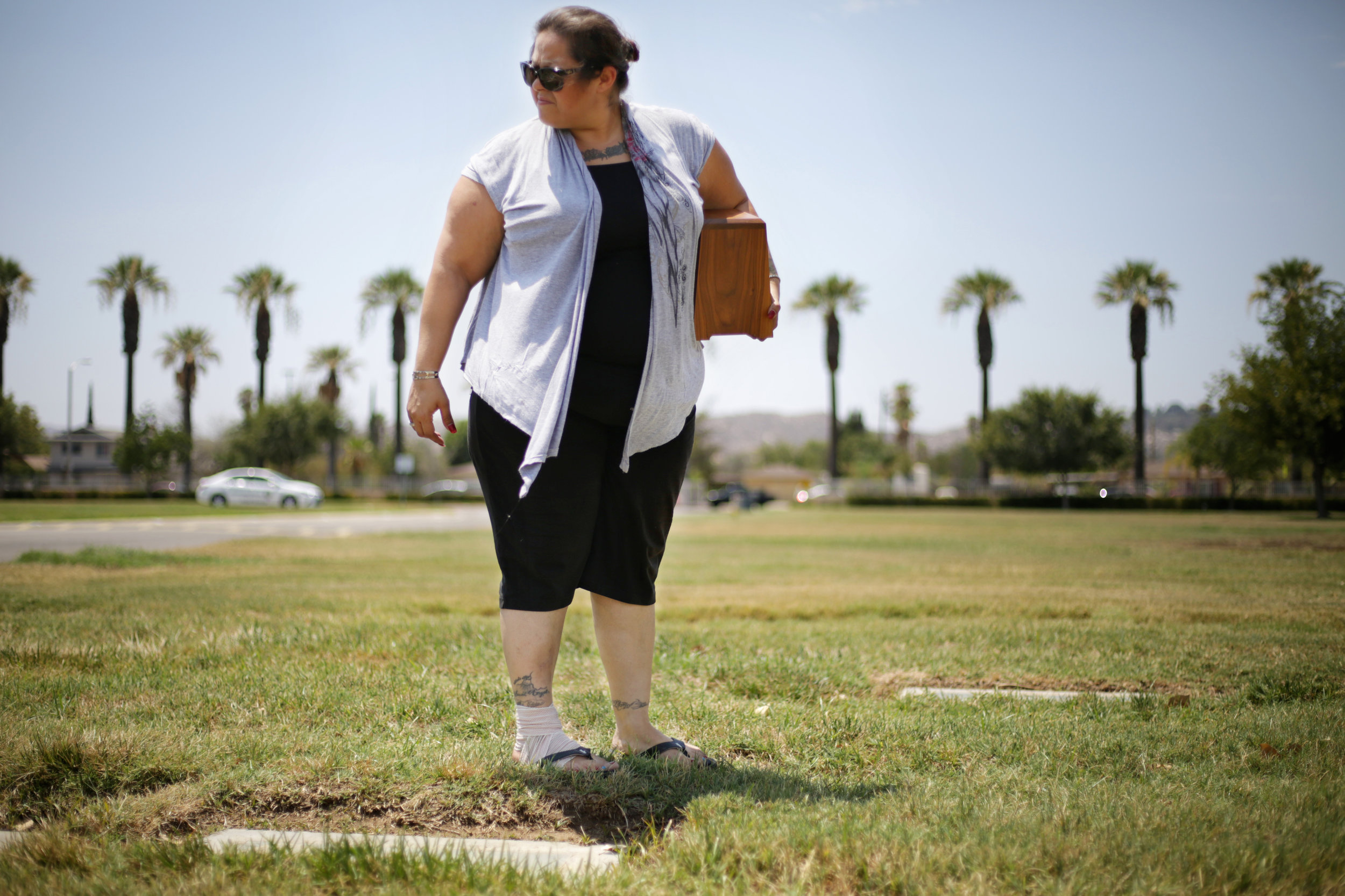 Antonia Rios, carries her mother's ashes through a cemetery to visit her fathers grave August, 2016. Rios's mother passed away a couple months ago and her father died when she was very young. Rios is a mother of seven children and she strives to reconnect with all her kids after they were in foster care for four years.
