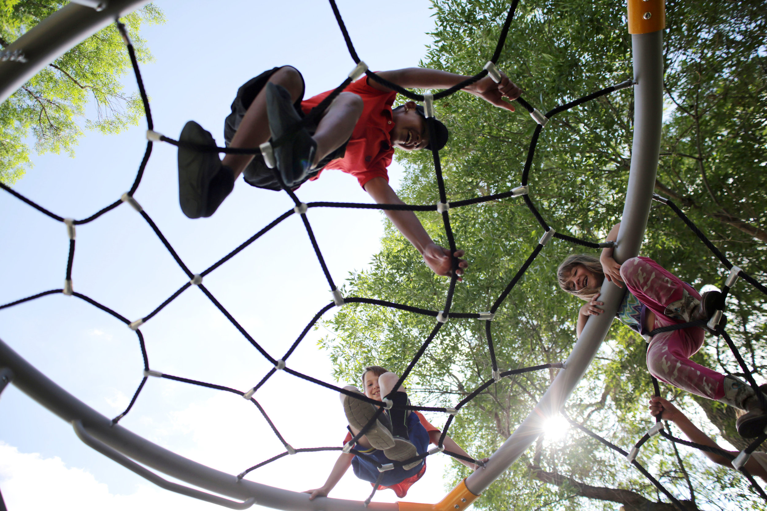Steven Burton 11, bottom, Mario Hernandez 14, top, and Rylee Burton 6, climb on a spider web at Lincoln Park in Greeley, Colorado, June 2017. Steven, Mario and Rylee were really excited to play on the playground at Lincoln Park as it just re-opened after being under construction (Greeley Tribune Newspaper).