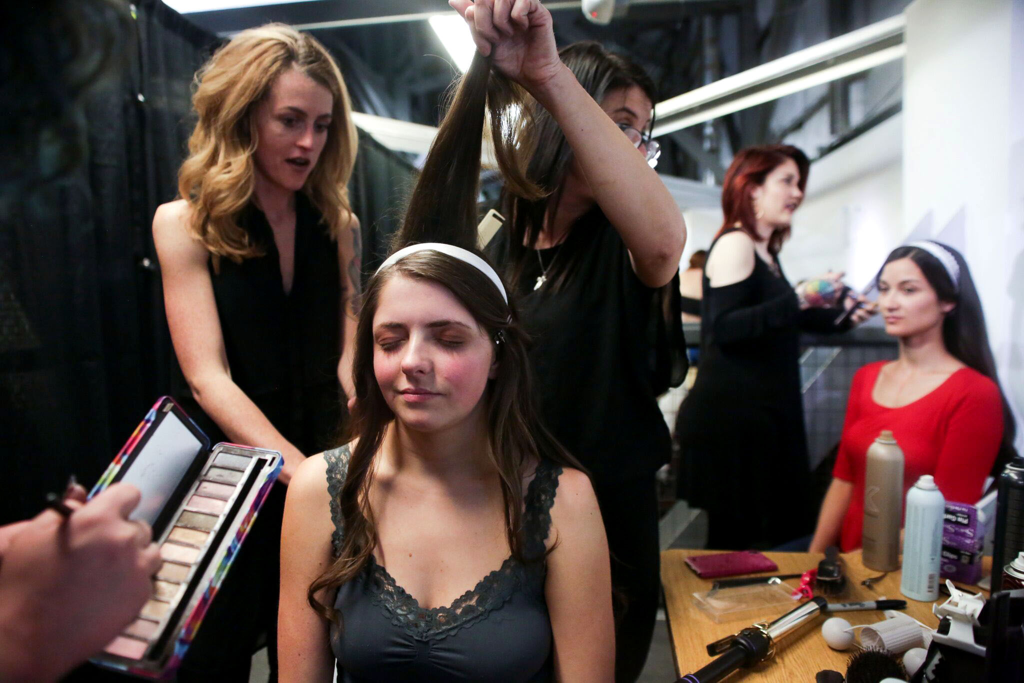 Makeup artists and hairstylists get a model ready for the runway during Denver Fashion Week on March 18, 2018 at Wings Over the Rockies Air and Space Museum in Denver, Colorado.