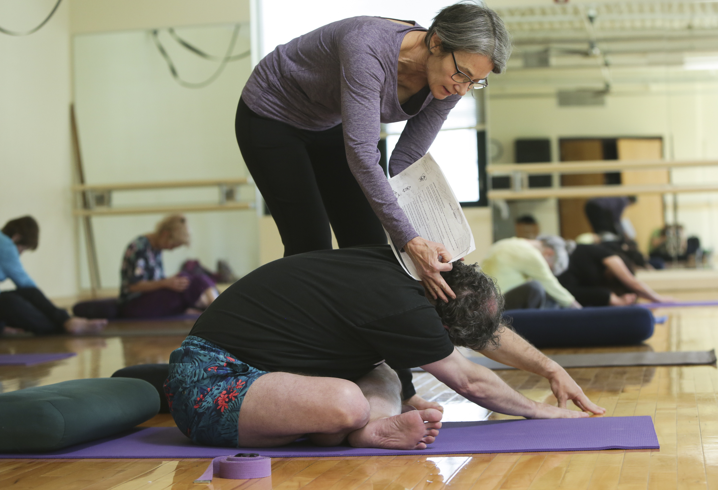 Wendy Zerin, a yoga instructor helps Kevin Pettit with a stretching exercise during a yoga class at the North Boulder Recreational Center, in Boulder, Colorado, on April 25, 2018. Everyone who attended this yoga class is apart of the program called Journey through Expand which provides recreation and leisure activities for adults with traumatic brain injuries.