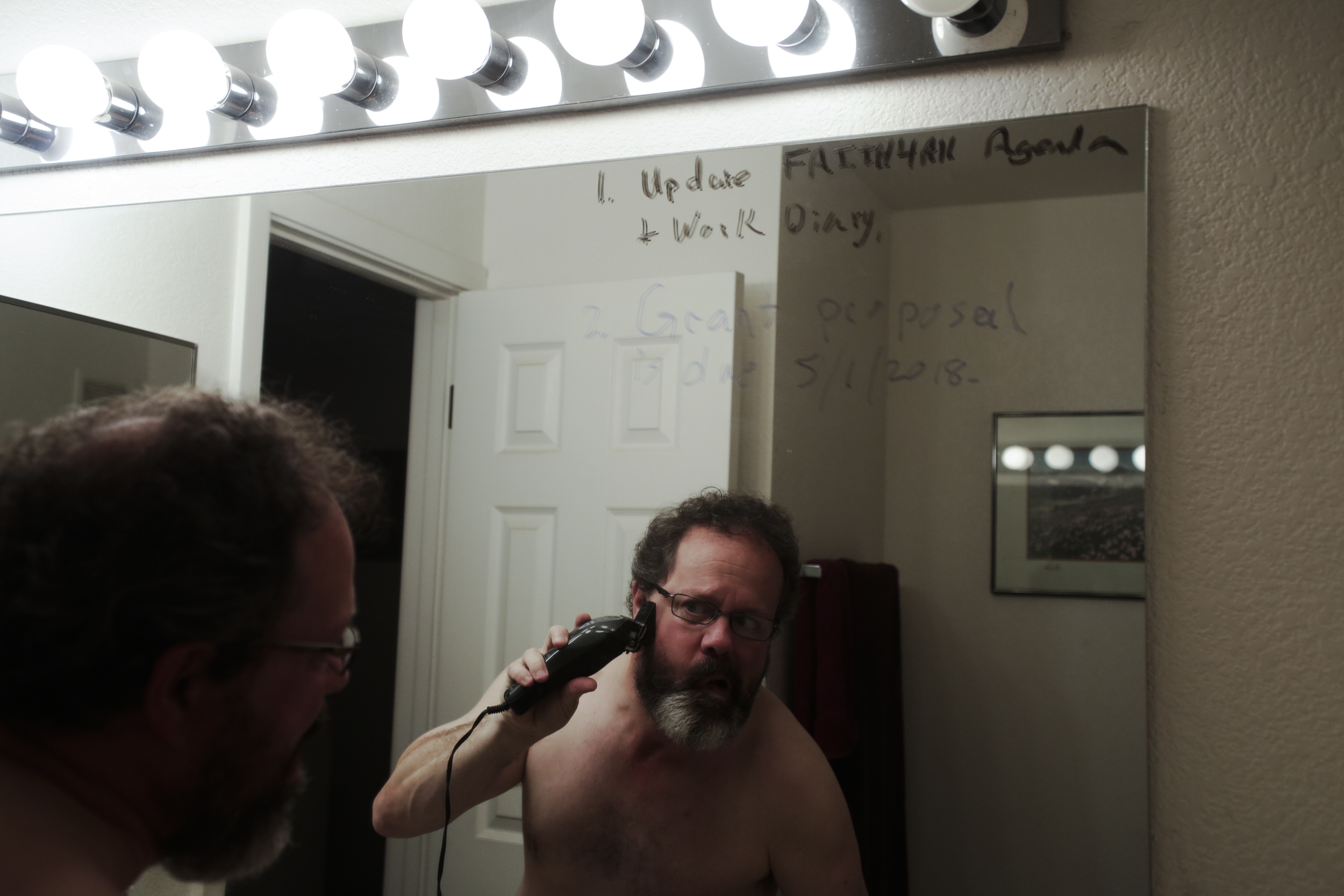 Kevin Pettit, 50, trims his beard in the bathroom of his house in Boulder, Colorado, on May 1, 2018. The writing on the mirror is notes that Pettit writes to himself so he can remember important things as he struggles greatly with his memory.