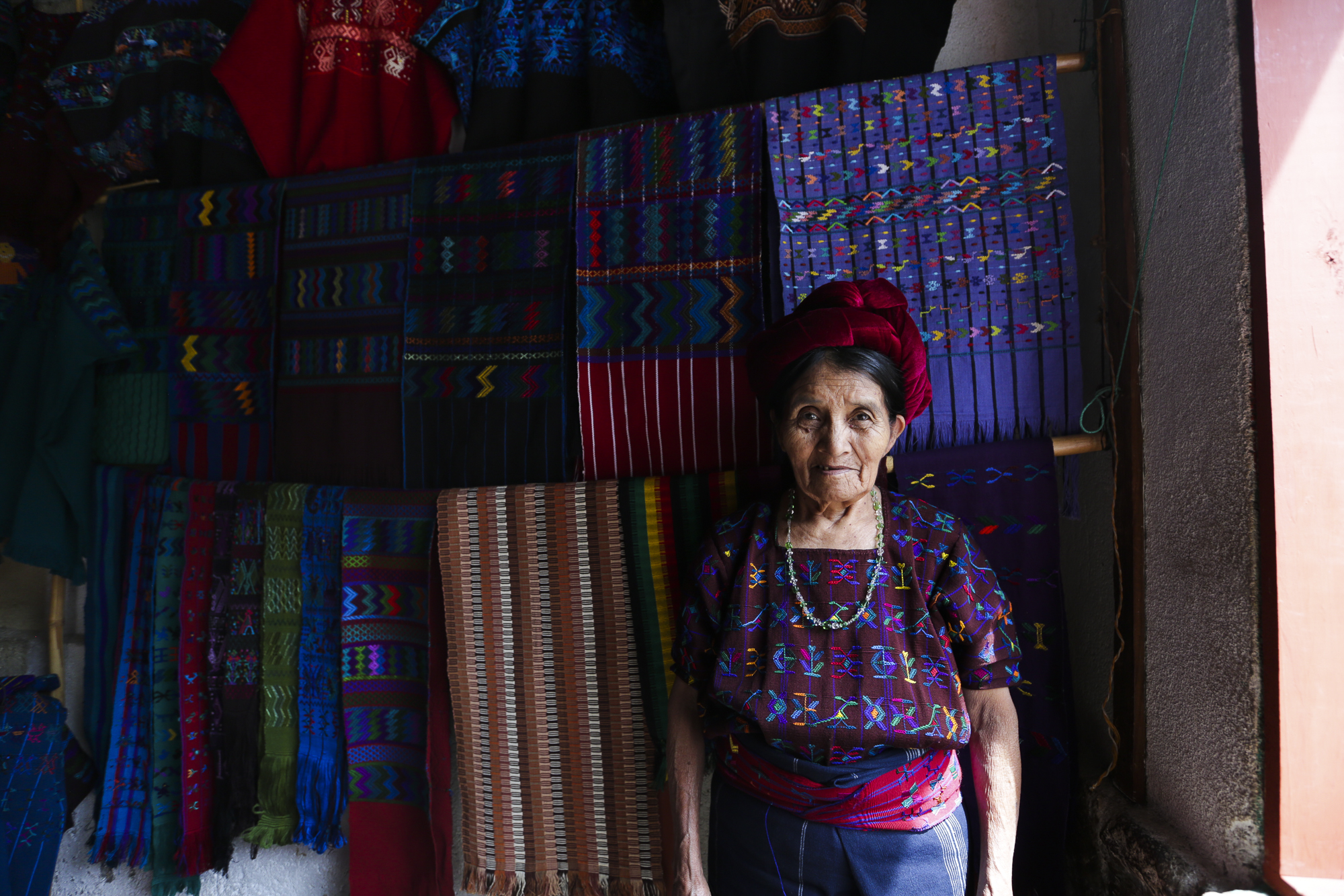 Catorina posses in front of her textiles in San Antonio Palopó, Guatemala, on August 4, 2018. Catorina said that one table cloth can take up to four months to make.