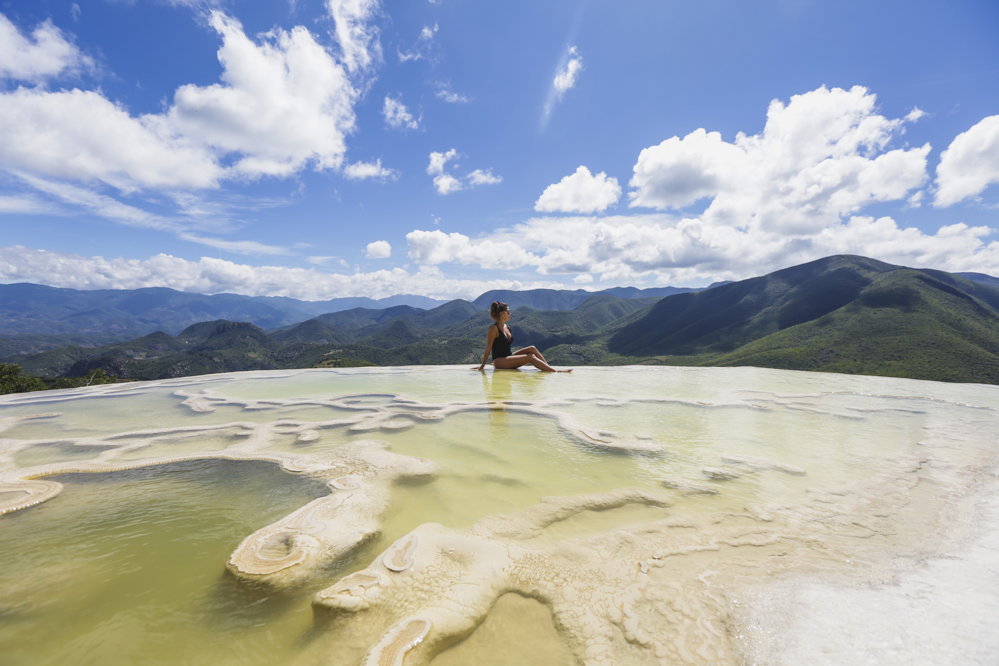 Victoria sits on the edge of Hierve el Agua, just outside of Oaxaca, Mexico, on October 30, 2018. Hierve el Agua is a set of natural rock formations in the that resemble cascades of water.These formations are created by fresh water springs, whose water is over-saturated with calcium carbonate and other minerals.