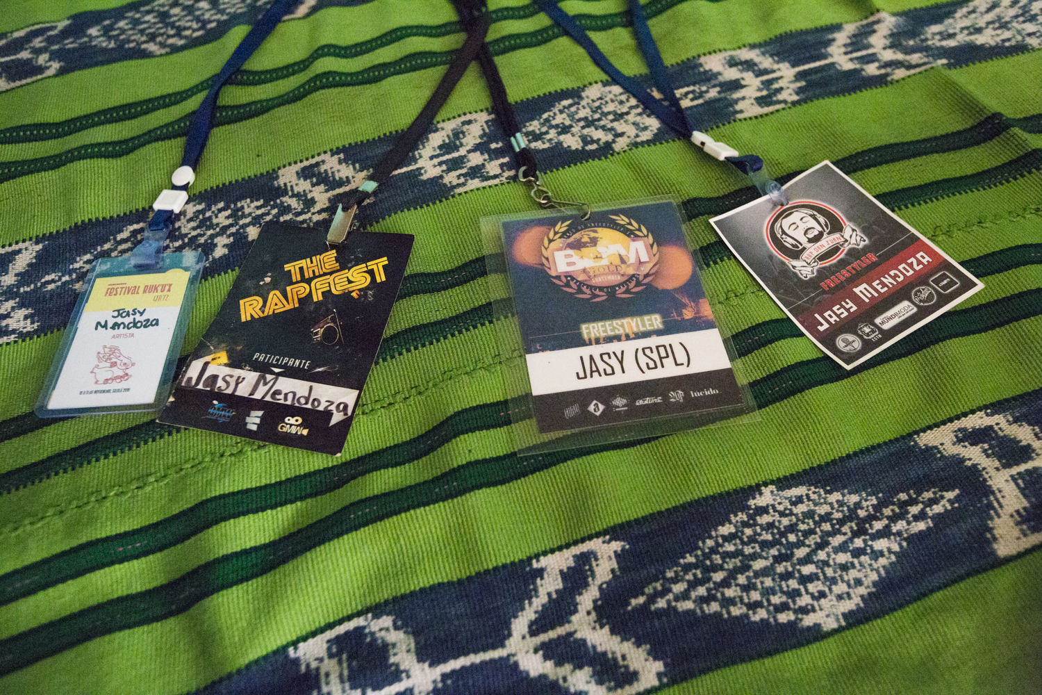 Detail shot of badges on Jasy Mendoza's bed, from some of the hip-hop events he has attended.