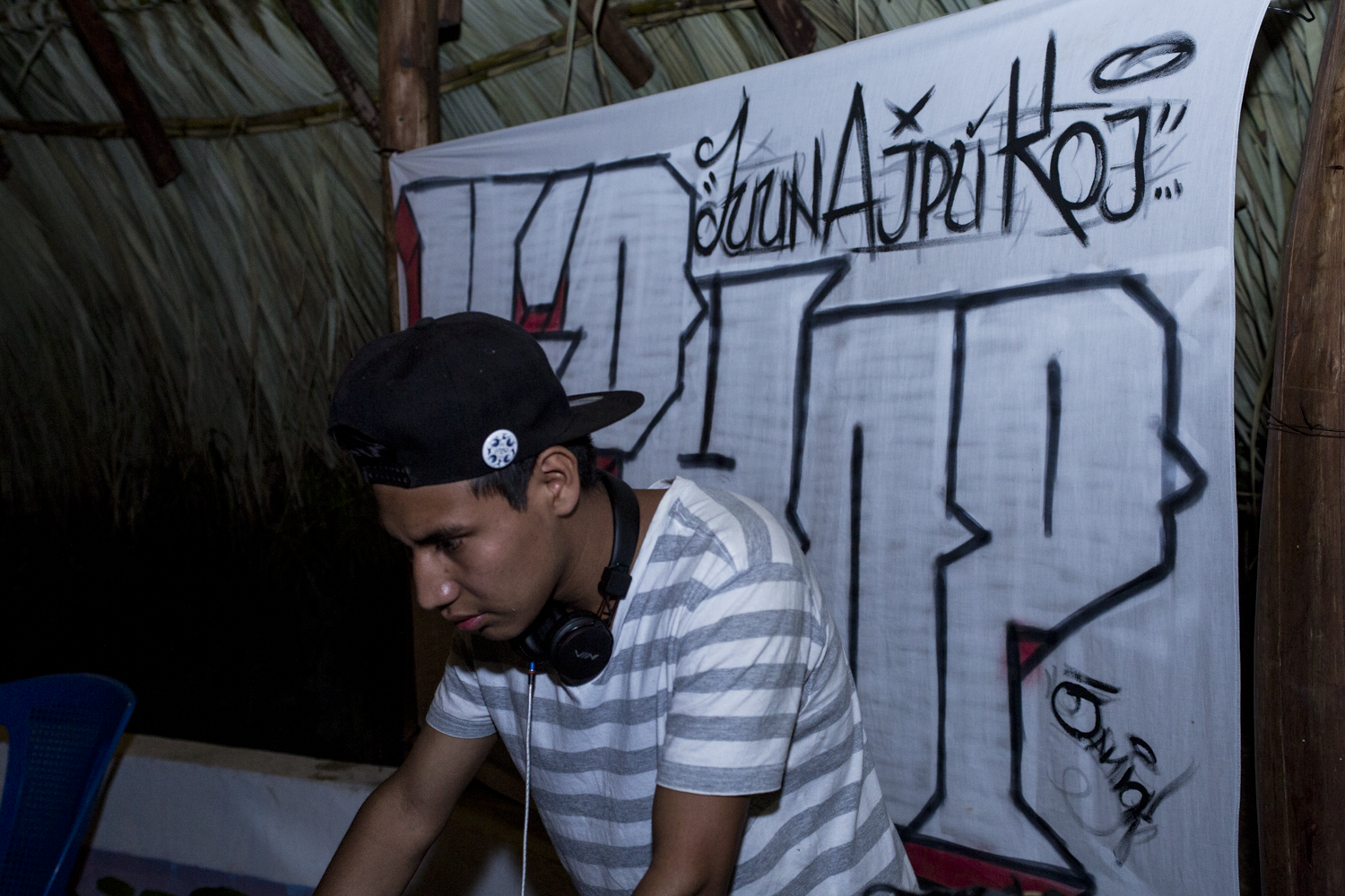 DJ Fer mixes beats as rappers come up to the stage to sing during a freestyle competition in San Marcos La Laguna, Lake Atitlán, on December 15, 2018.