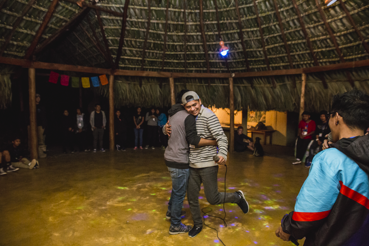 """Edwin Gomez """"DeThe"""" left, and Ermar Sumoza """"13"""" right, hug after battling each other in a freestyle in San Marcos La Laguna, Lake Atitlán, on December 15, 2018."""