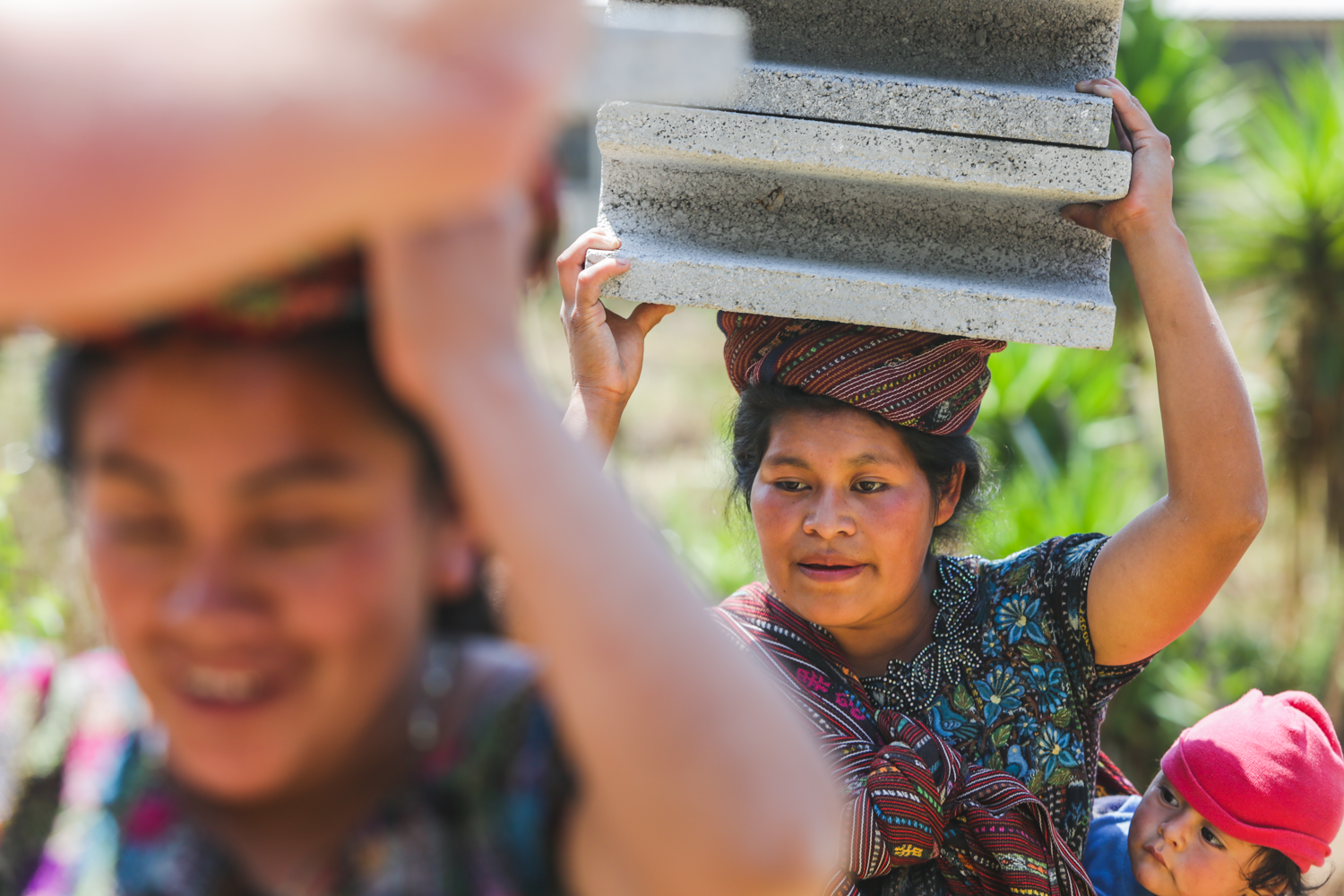 Mothers from Peña Blanca help carry concrete blocks to the Peña Blanca Preschool for volunteers to help build a wall around the school to protect the area. Peña Blanca is a small town in rural Guatemala primarily inhibited by indigenous families.