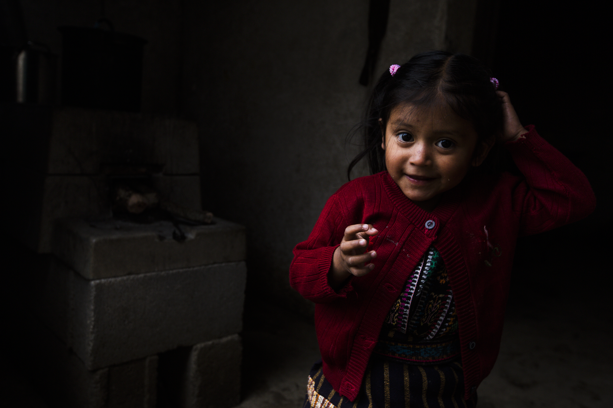 A little girl plays outside of her house with her family in Peña Blanca, Guatemala.