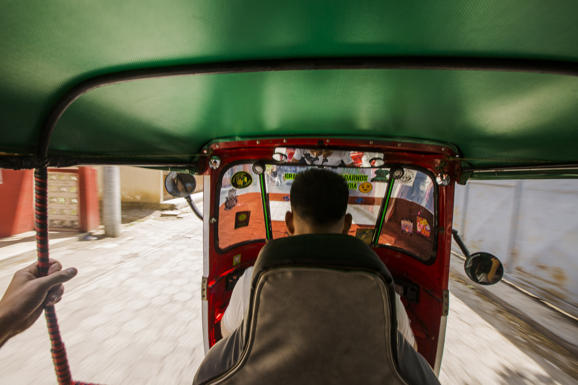 View from the back of a tuk tuk in San Pedro La Laguna, Guatemala. Tuk tuks are a common form of transportation in Guatemala. They are very convenient as they can be found on almost every street and they can fit through small alleyways.
