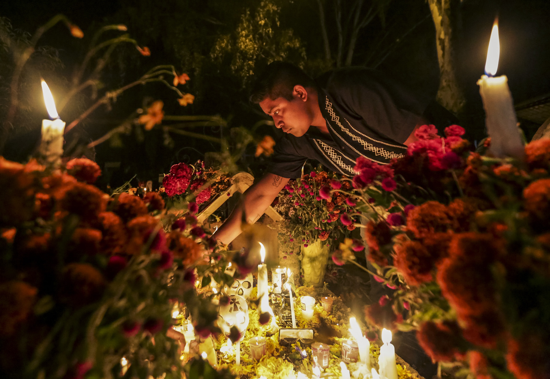 A man lights candles on a family members' grave during Dîa de Muertos (Day of the Dead) in Oaxaca, Mexico, on October 31, 2018. Dîa de Muertos is a Mexican holiday where family and friends gather to celebrate and remember people who have died, and help support their spiritual journey.