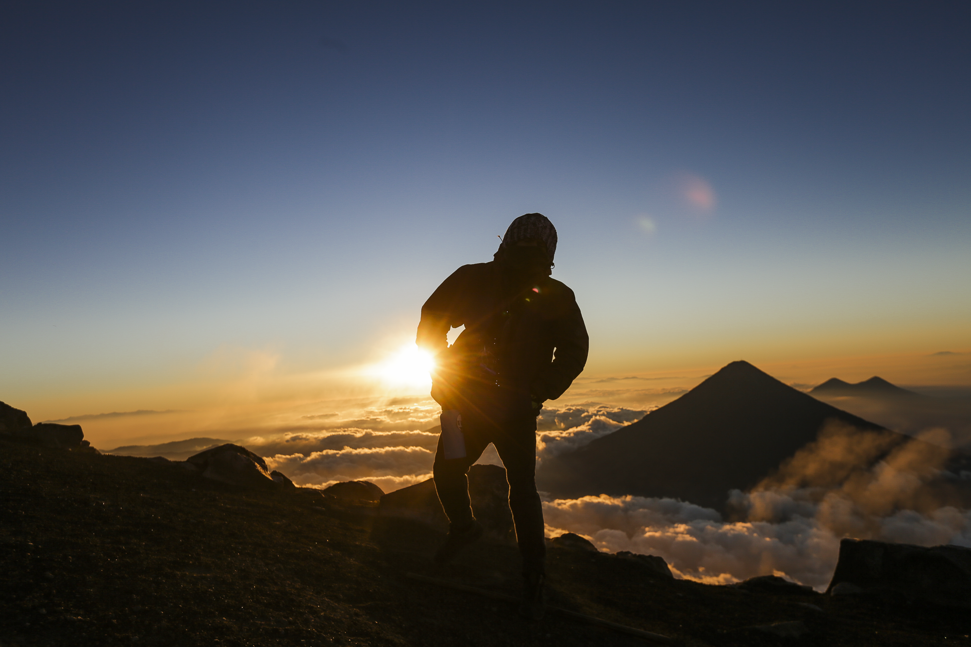 Jason Gegere reaches the top of Volcán Acatenango at 5:00 am just as the sun begins the rise. Acatenago lies next to Volcán Fuego, which an active volcano that erupts constantly throughout the day and night.