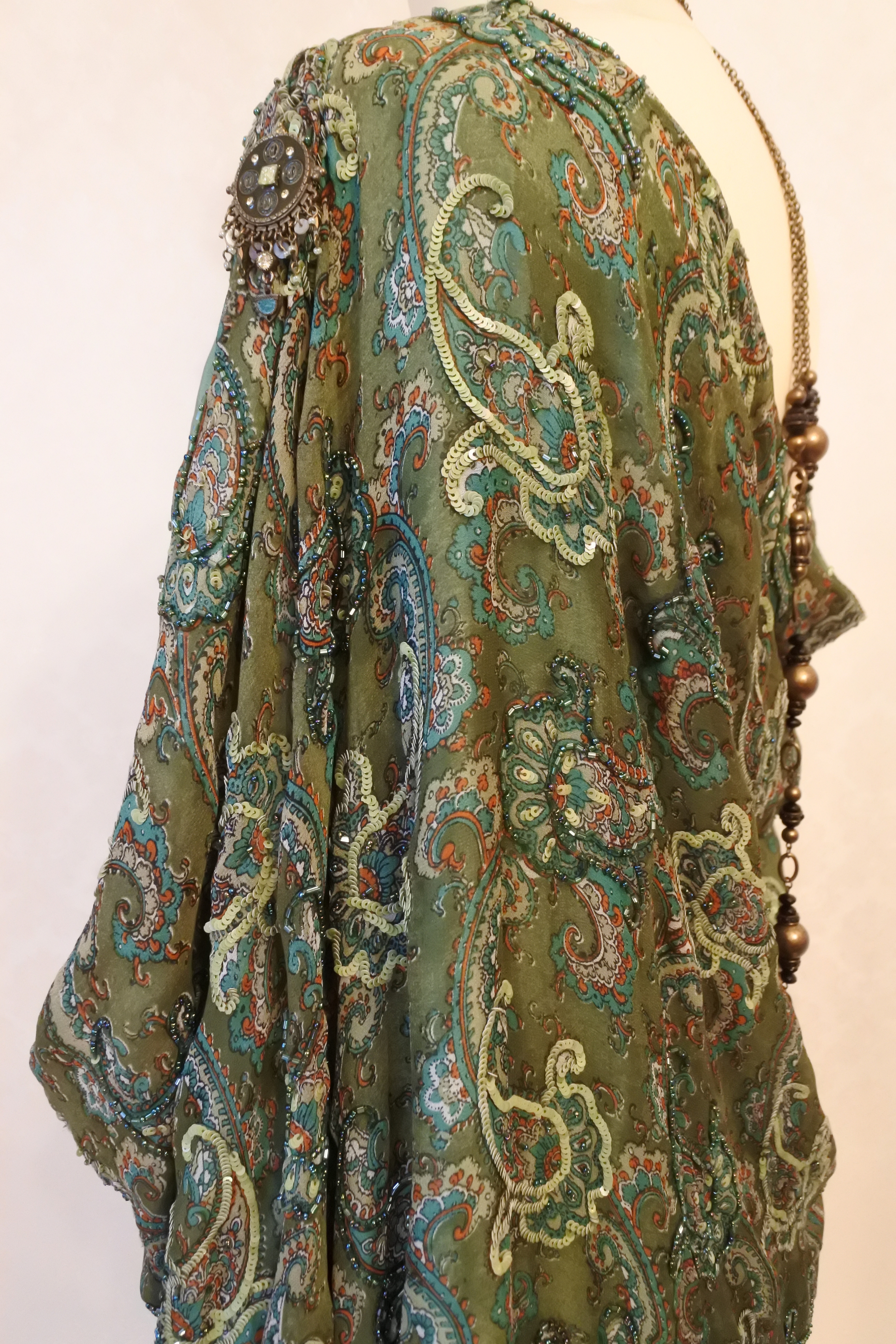 Draped beaded silk with shoulder detail.