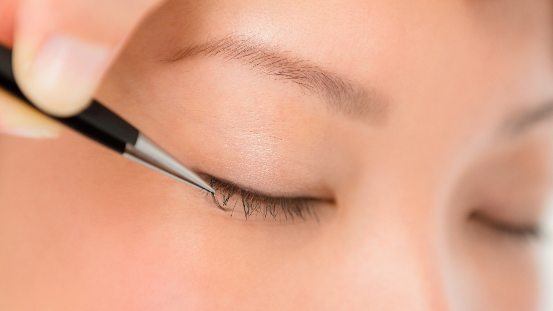 Lashes being added to a client's lash line by a technician using tweezers and adhesive
