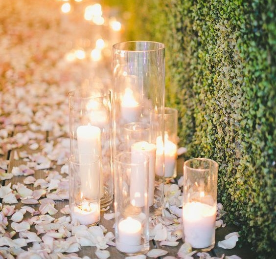 Petals surrounding candles along green wall. Image:http://www.huffingtonpost.com/entry/18-impossibly-romantic-ways-to-use-candles-at-your-wedding_us_55e4cd01e4b0c818f618e7f4?