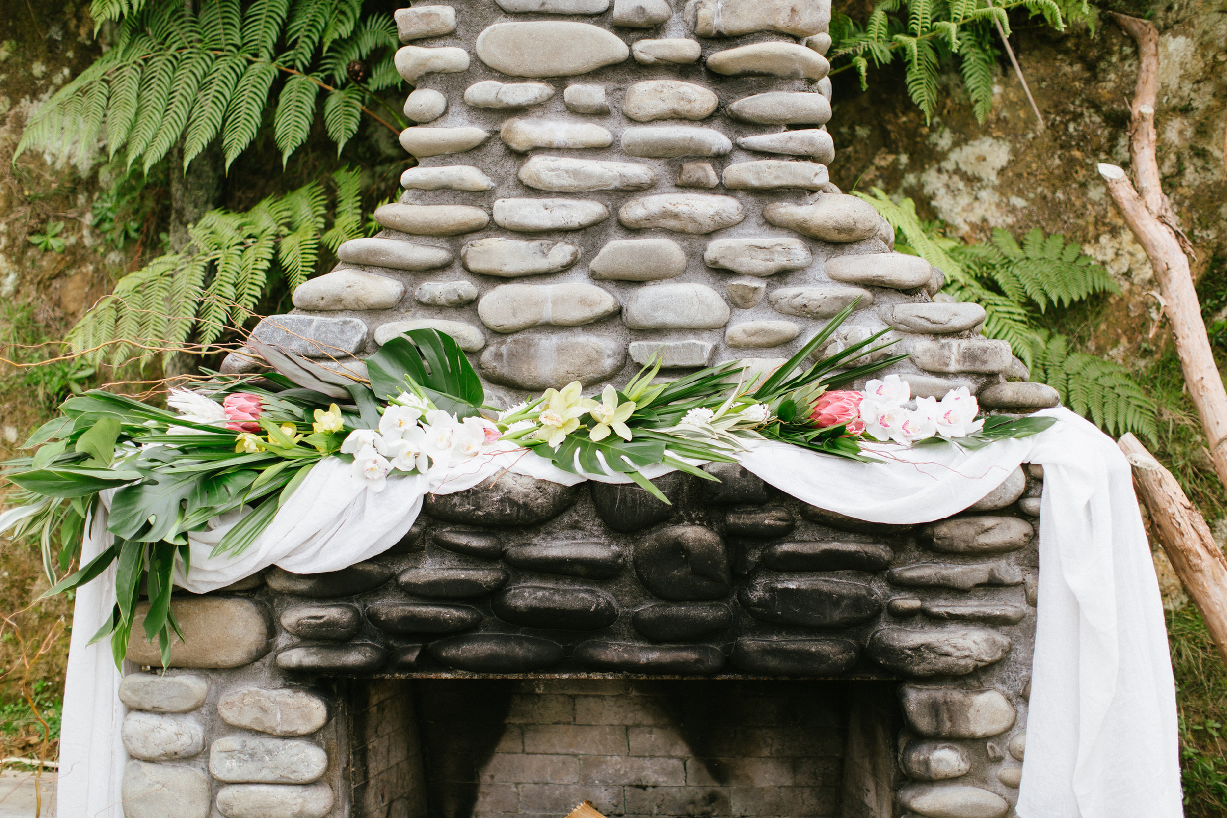 Tropical Wedding Protea florist NZ Wedding Orchid Rose Willow Pink Pineapple Photo shoot Fireplace Macrame Woodroyd Estate