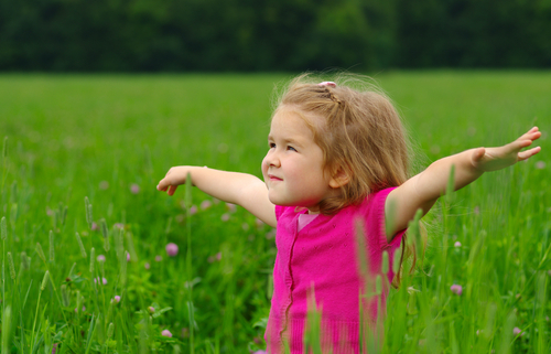 little girl in a field with arms out