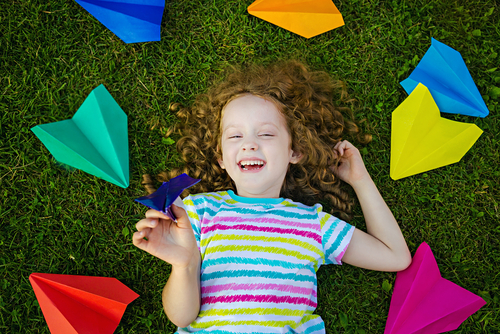 girl laying on ground with colorful paper airplanes